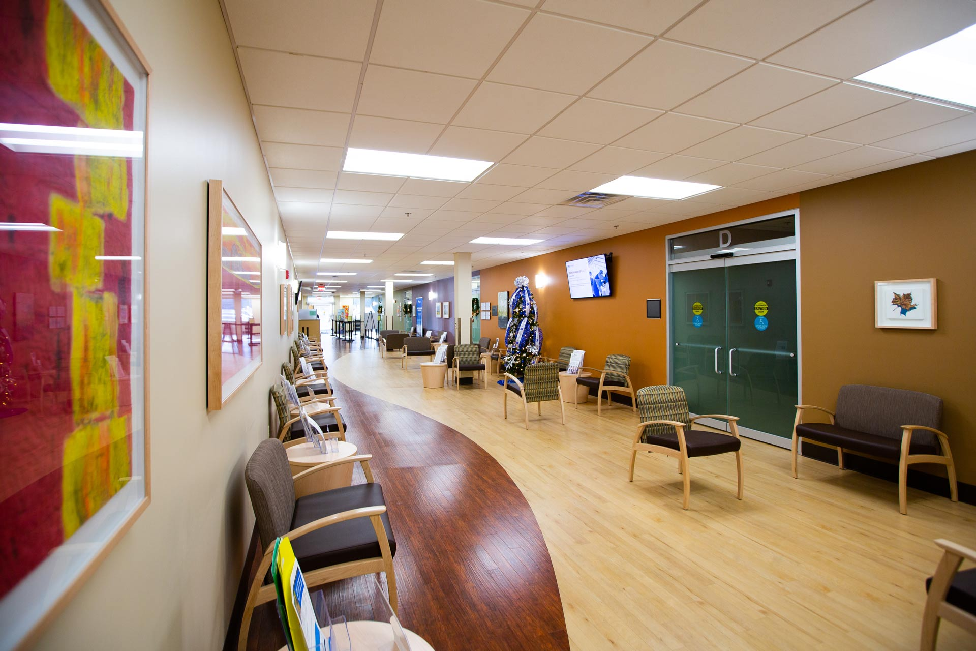 An interior view of the lobby of the UK HealthCare Barnstable Brown Diabetes Center where there is a spread of chairs and tables, paintings on the wall, various signs and informational monitors.