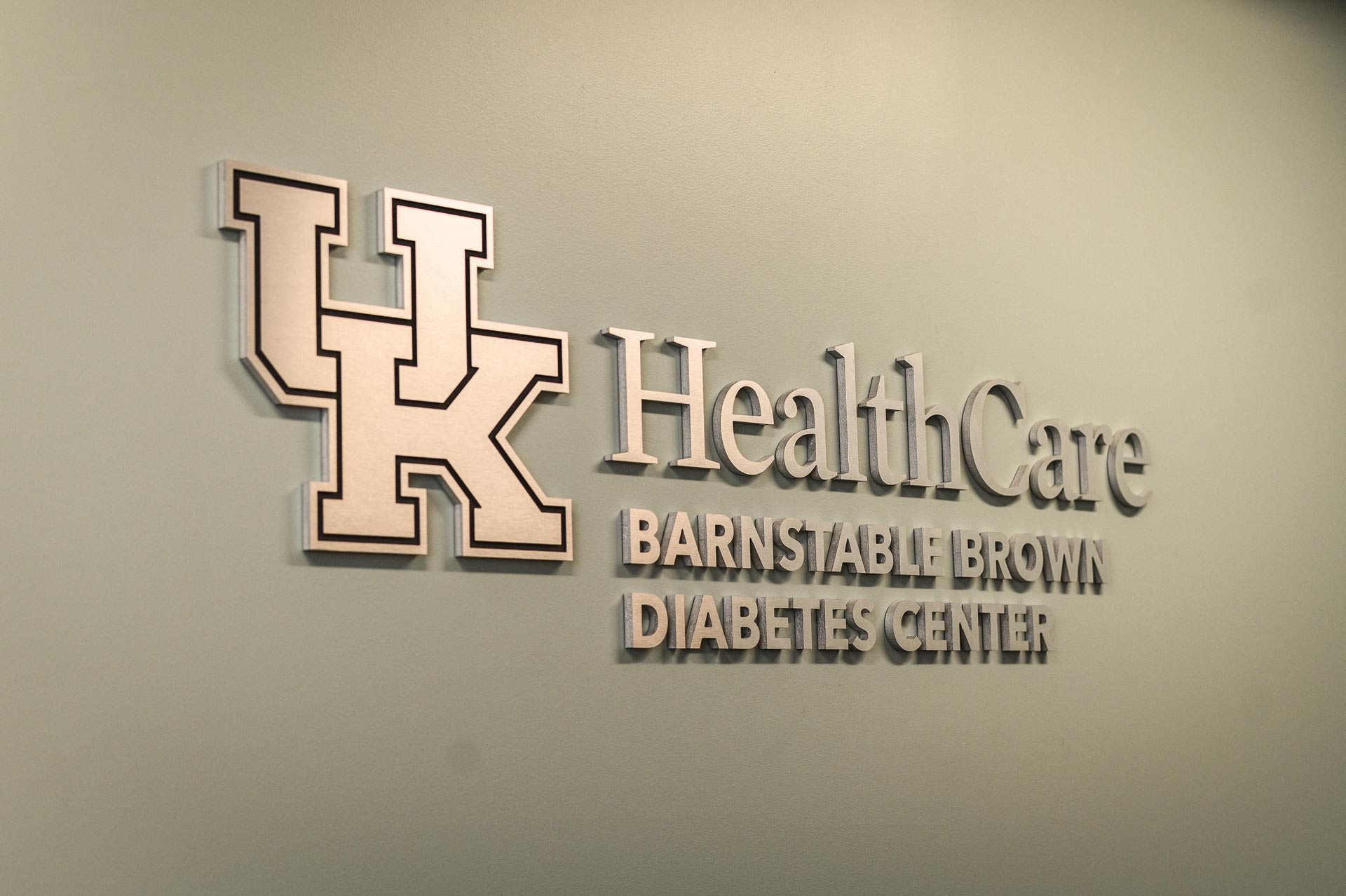 "A silver sign reading ""UK HealthCare Barnstable Brown Diabetes Center,"" mounted on the interior wall of a building."
