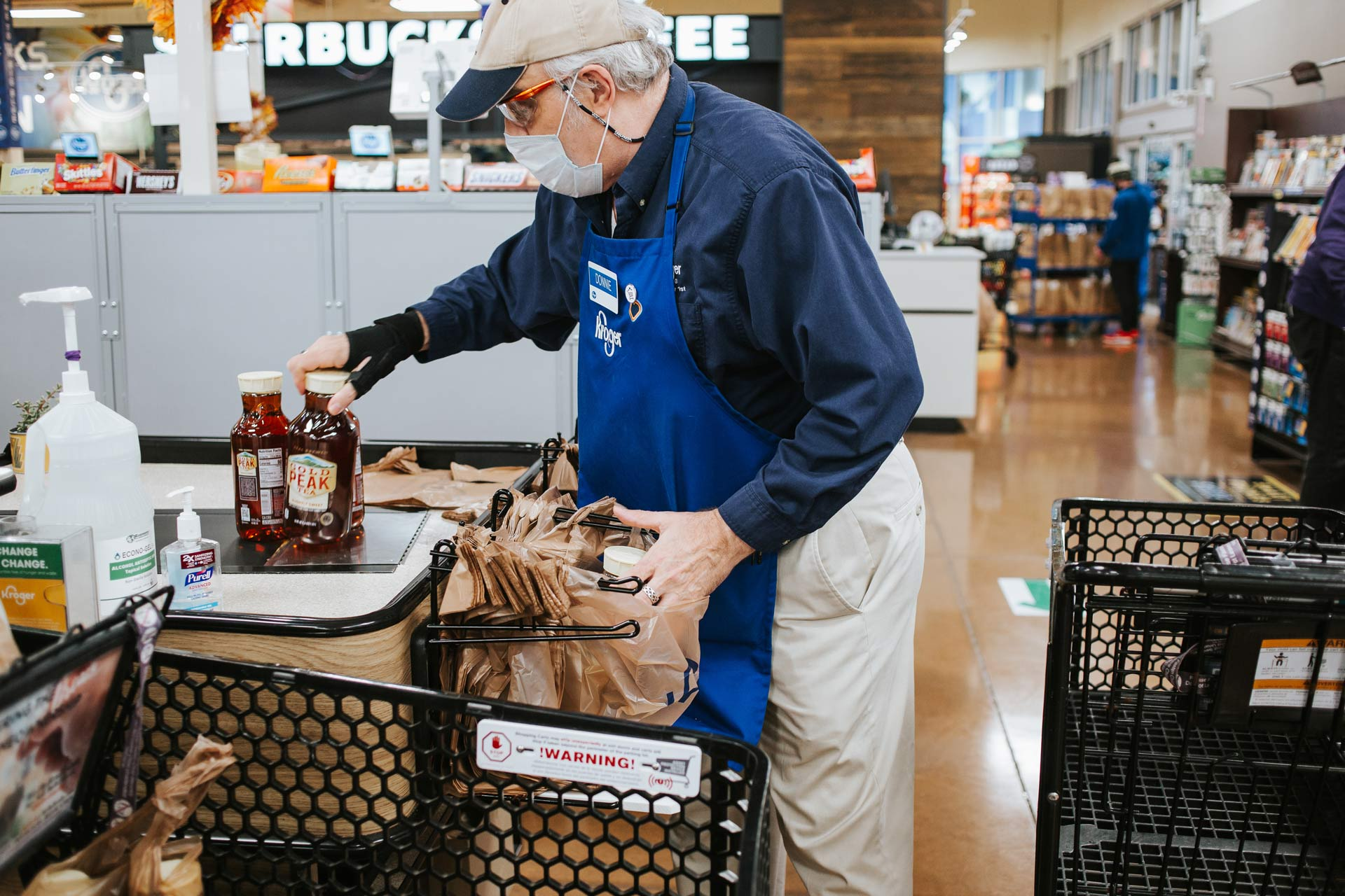 Donald is putting groceries in a plastic bag at a Kroger supermarket. He is wearing a facemask, a khaki baseball cap and a blue Kroger apron and nametag.