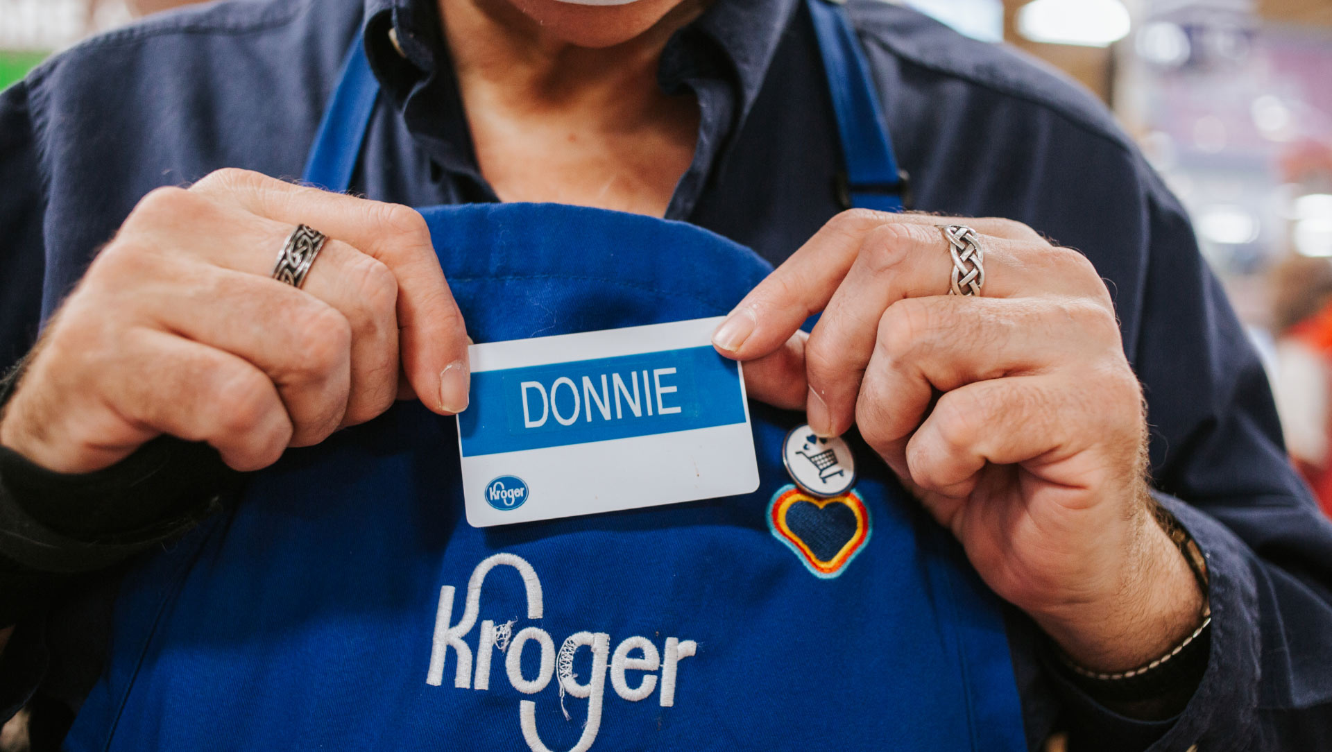 "Donald holding his name badge, which says ""Donnie"" and is attached to his Kroger employee apron, in front of his chest."