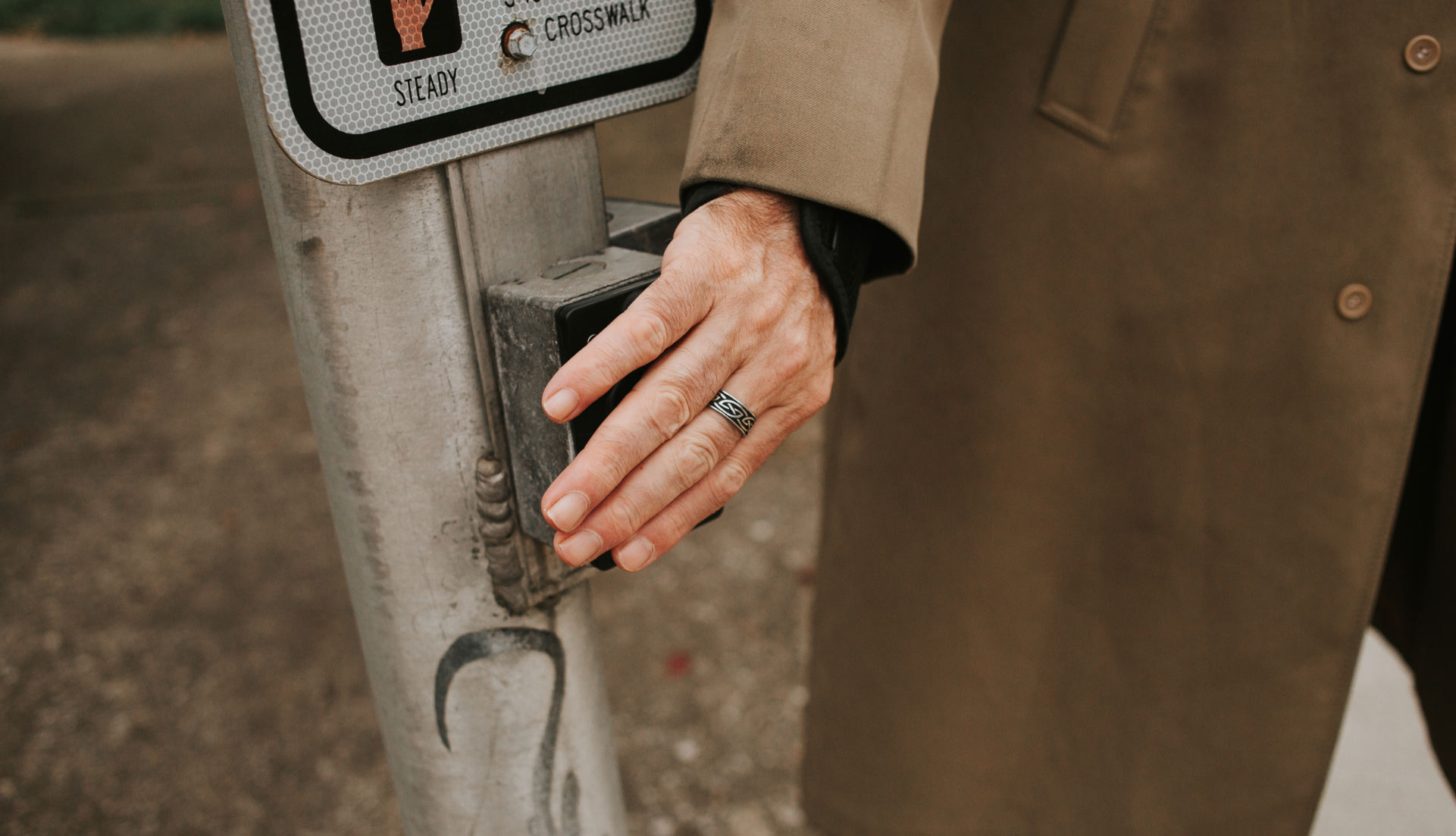 Donald places his hand on the pedestrian call button at a street crossing. He has a ring on his middle finger.
