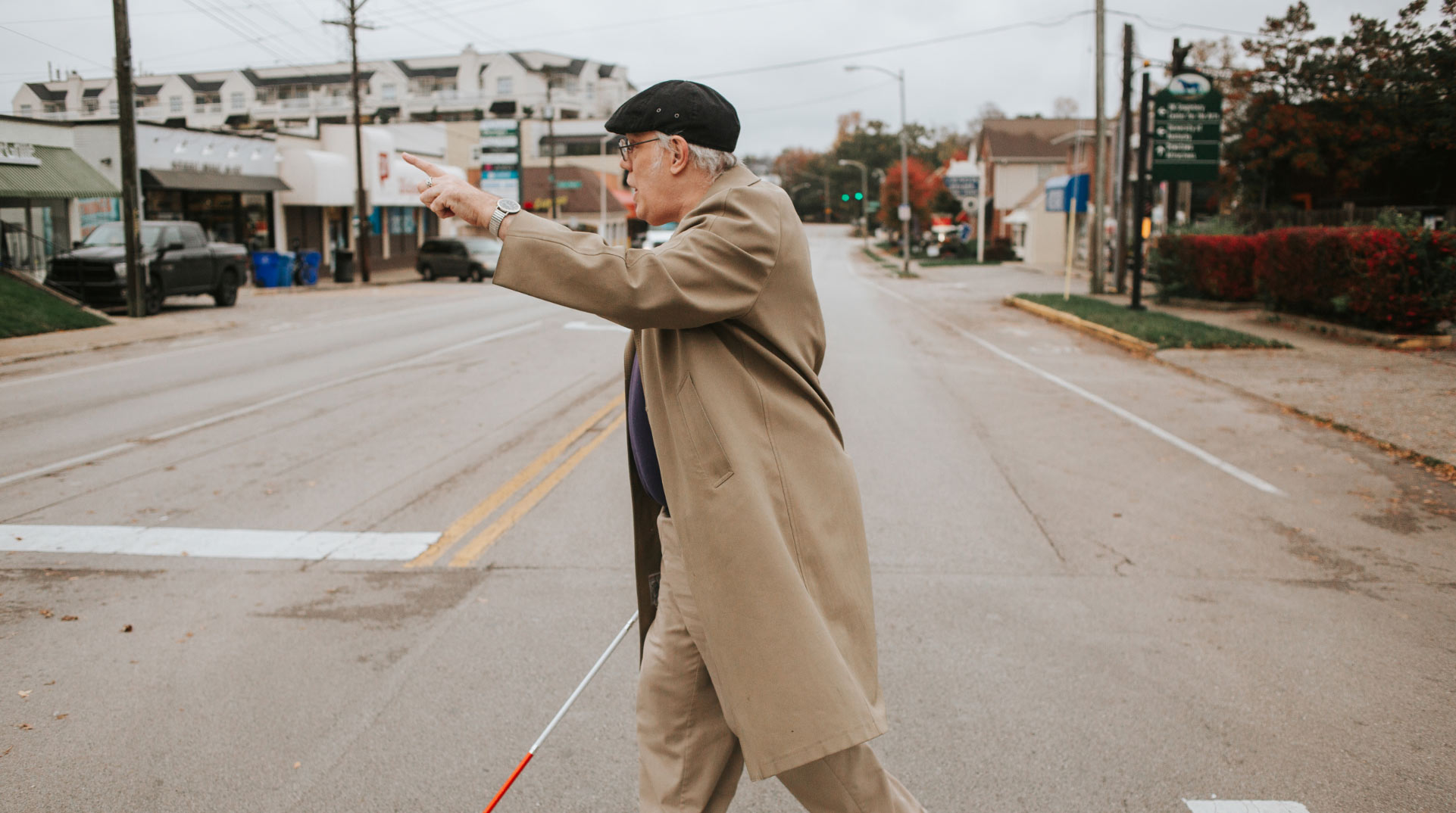 Donald is crossing the street using his cane, and points forward ahead of him.