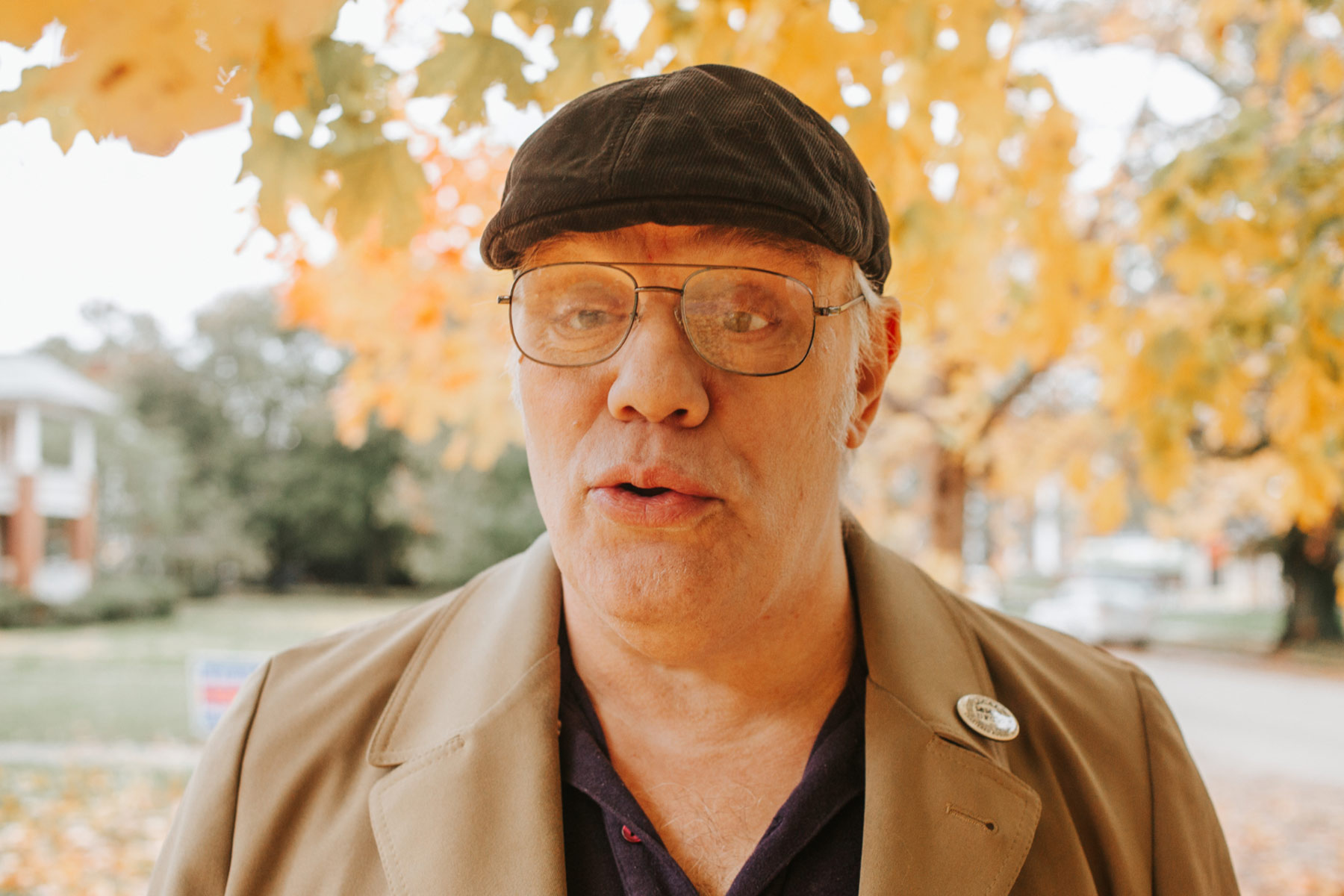 Donald Young, an elderly white man, stands in an outdoor setting under a tree. He is wearing a black ivy hat with black-framed spectacles and a brown coat.
