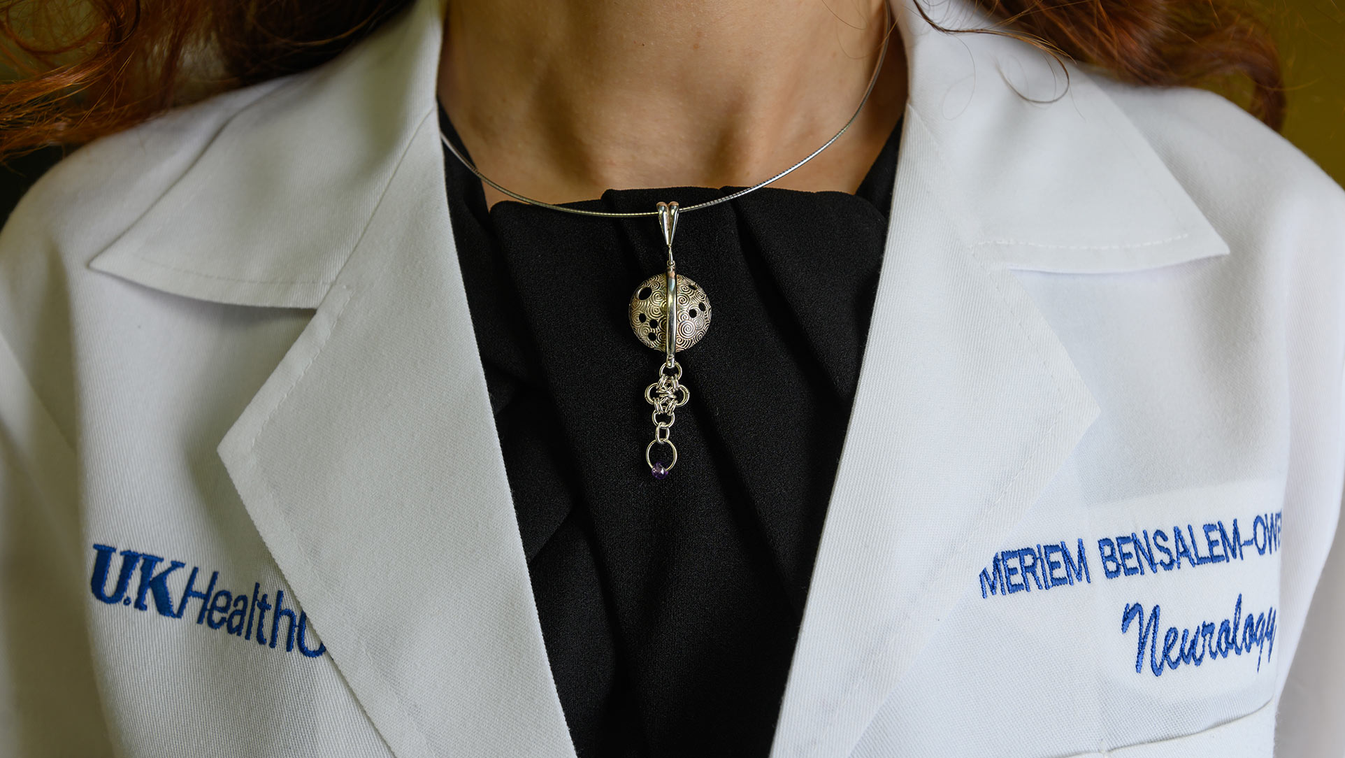 A close-up of a necklace that has a circular pendant with holes representing the brain, and a piece of other circles attached to it.