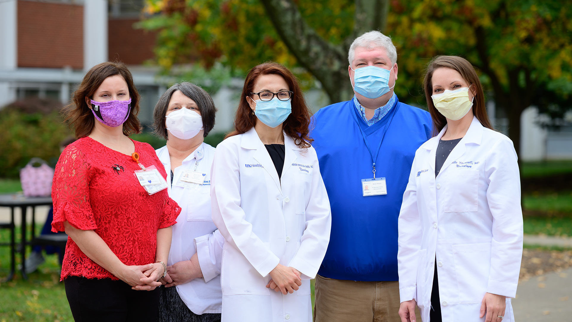 Dr Bensalem-Owen and four members of her team—three middle-aged white women and a middle aged white man—are standing in an outside area setting with their facemasks on.