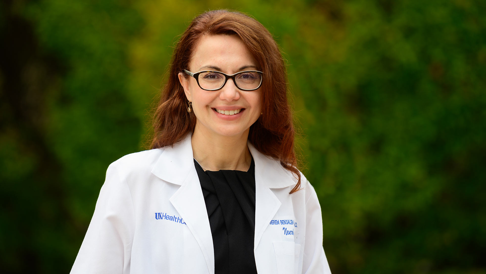 Dr. Bensalem-Owen stands with a broad smile in an outside setting.