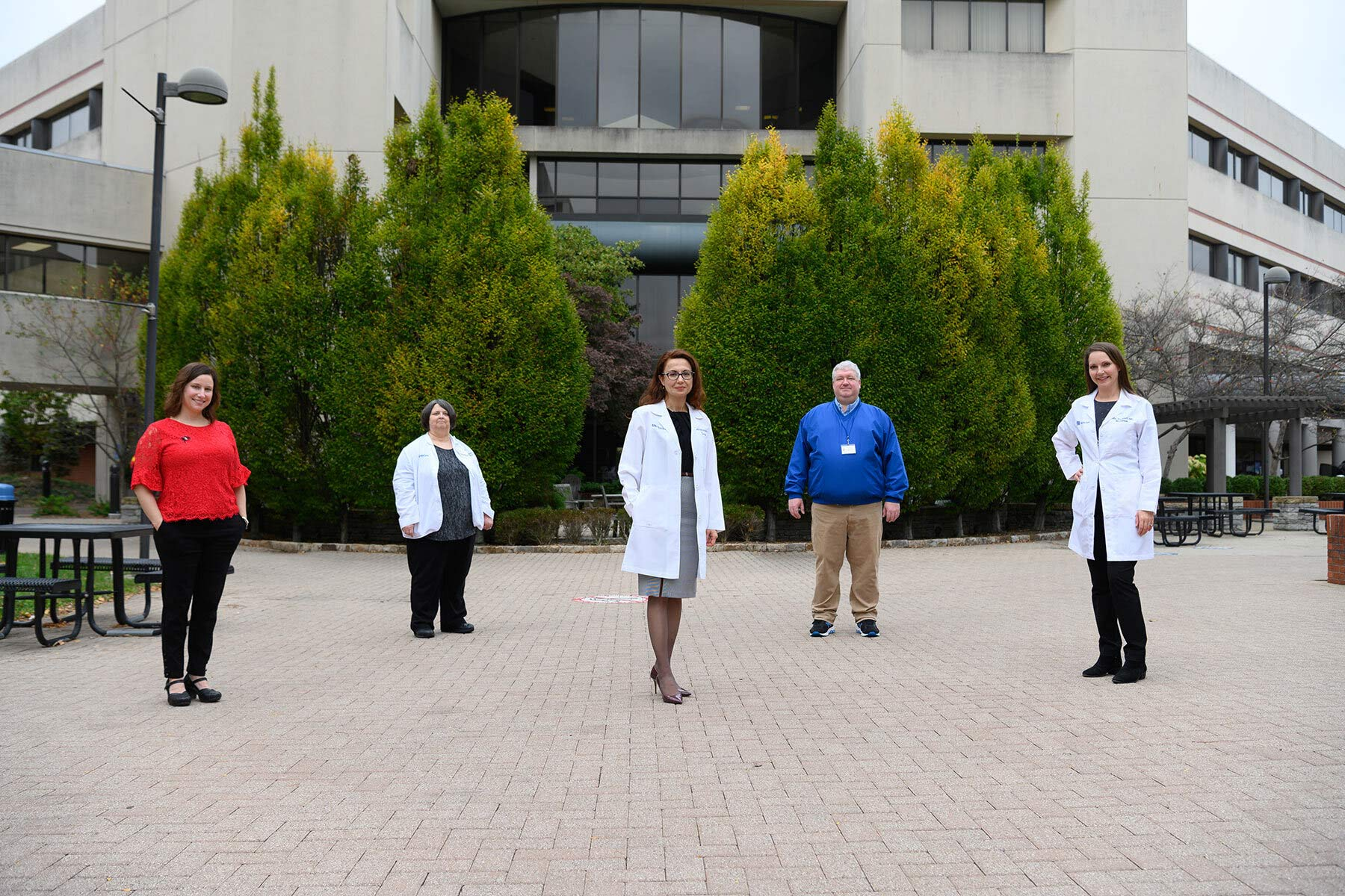 Dr. Meriem Bensalem-Owen, a middle-aged white woman with red hair, stands in an outside setting area with two of her colleagues: a middle-aged white man and an elderly white woman. Dr. Bensalem-Owen is wearing a white doctor's coat, a grey skirt and black framed glasses with a black blouse.