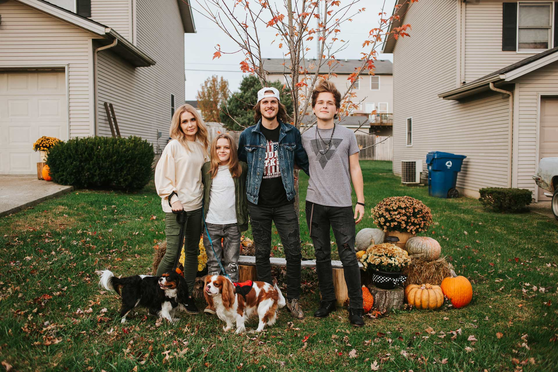 Evan standing side by side with his family and two dogs. On his right his mother, Krystena, smiles softly. On his left are his brothers, tall young adult white boys with medium to long brown hair. One is wearing a white baseball cap backwards and a denim jacket with black jeans. The other is wearing a grey shirt with black jeans. All are smiling.