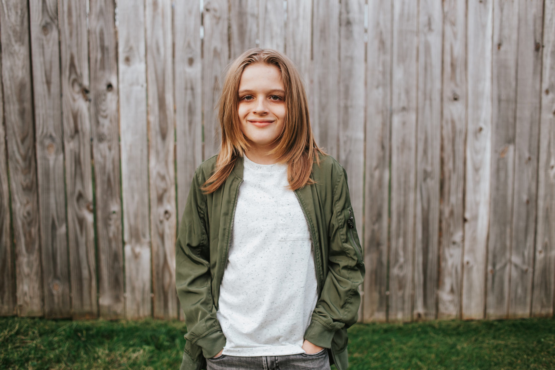 Evan Richards is a pre-teen white boy with long blonde hair and a broad smile. He is wearing a white shirt and an olive green jacket in an outside setting.