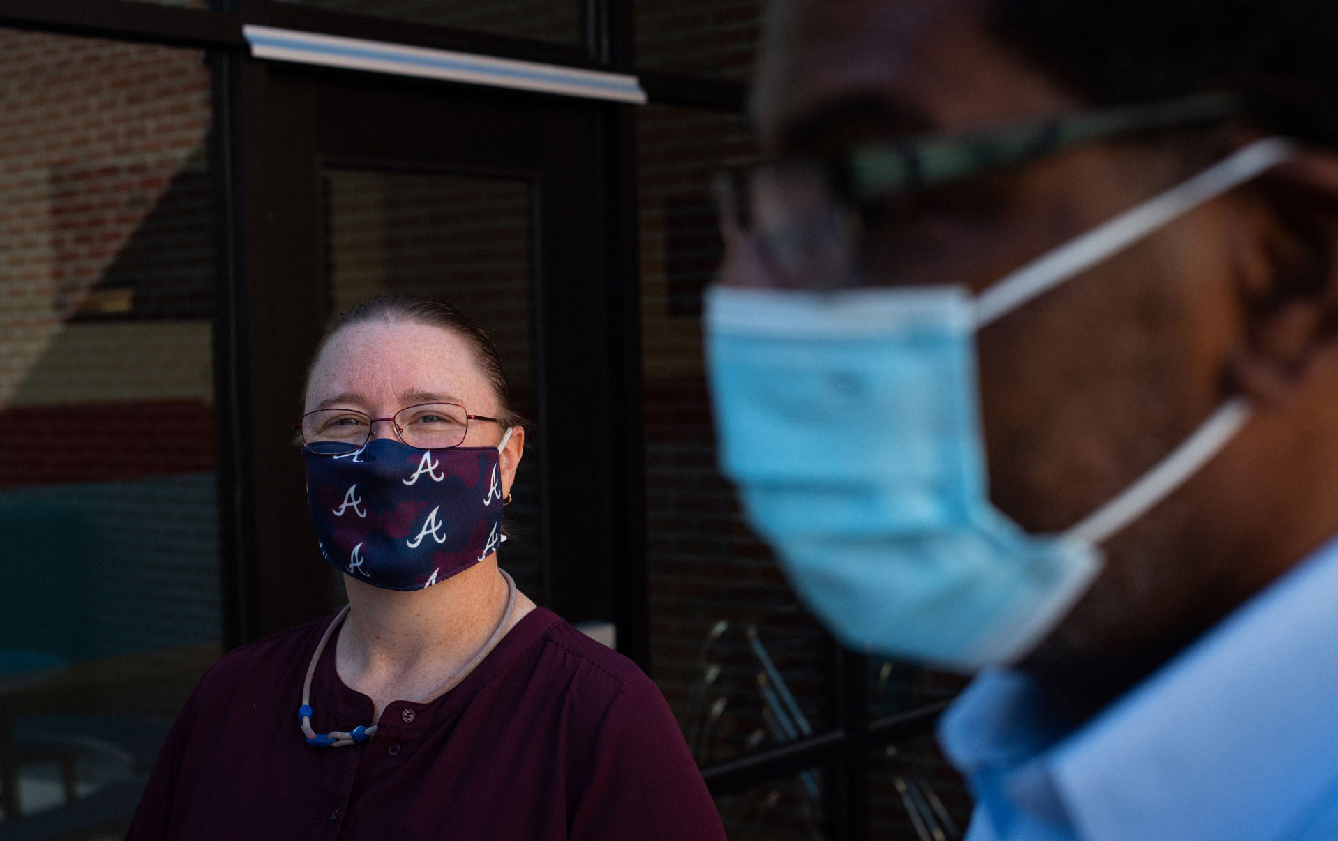 Marci Smith, a middle-aged white woman, is shown in focus on the left side of the photo. She has brown hair, pulled back in a ponytail, and is wearing glasses and red blouse. She is wearing a maroon and blue face mask. Ivan is in the foreground of the photo, out of focus and wearing a blue surgical mask.