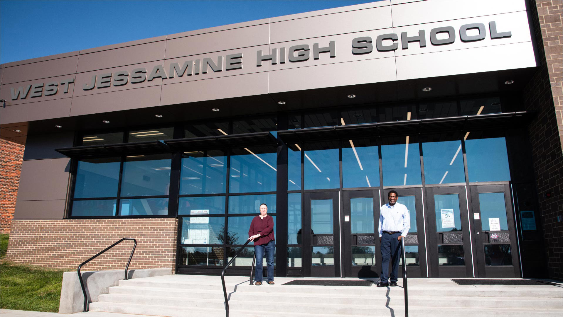 Ivan and Marci stand on the front steps of West Jessamine High School. Both are holding onto the handrails of the steps and smiling.