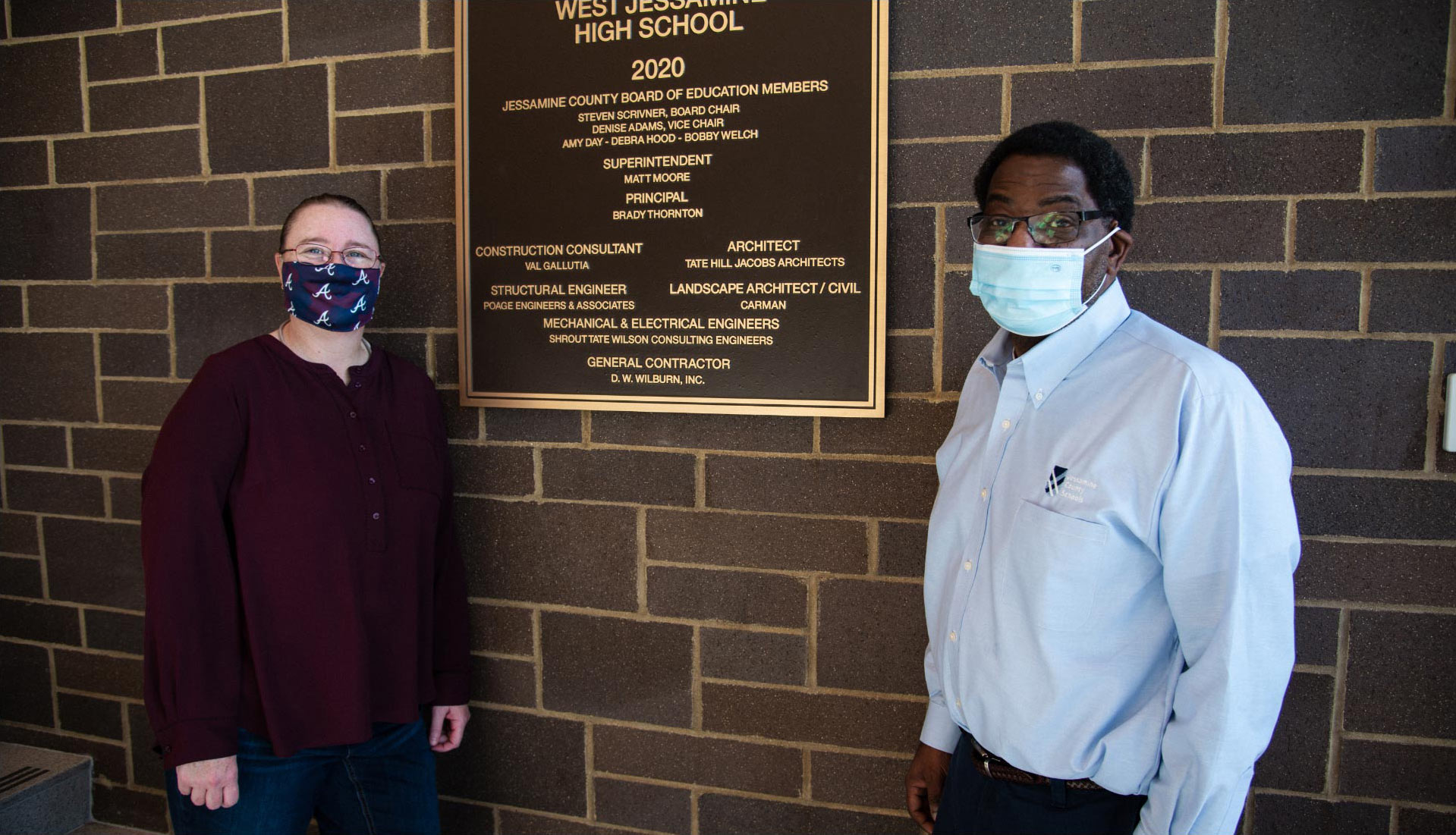 Ivan and Marci stand next to a West Jessamine High School plaque that's attached to a brick wall inside the school. Both are wearing masks and looking at the camera.