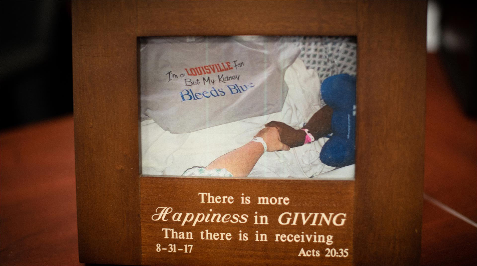 "A photo in a frame, showing Ivan and Marci at the hospital. They are holding hands and wearing hospital gowns. Only their arms are visible. Draped over Ivan is a tee shirt that reads ""I'm a Louisville fan but my kidney bleeds blue."" The photo frame says ""There is more happiness in giving than there is in receiving."""