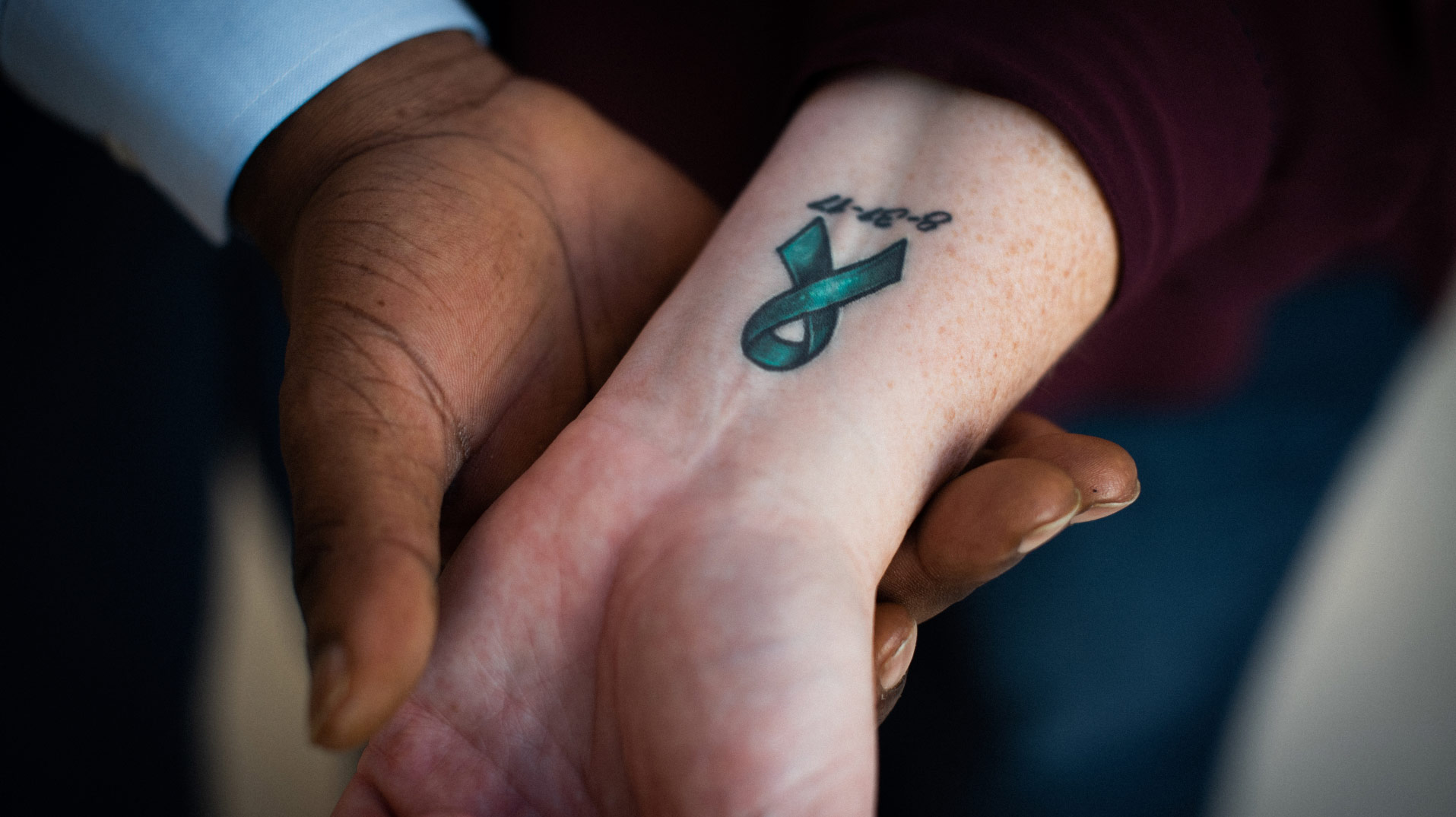 A close-up of the inside of Marci's wrist, which features a tattoo of a green ribbon and the date 8-31-17. Ivan is holding Marci's wrist in his hand.