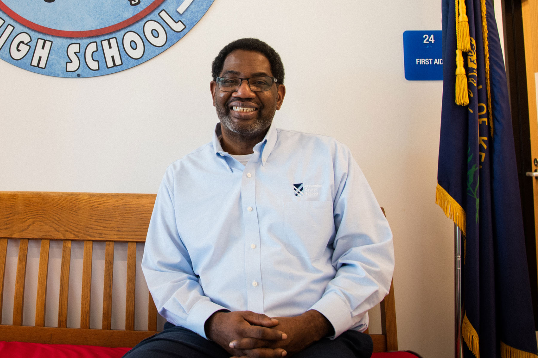 Ivan Graves, a 60-year-old Black man with short dark hair, black glasses, and a short, graying beard, sits on a bench in the hallway of a high school. He is wearing a light blue collared button-down shirt and is grinning.