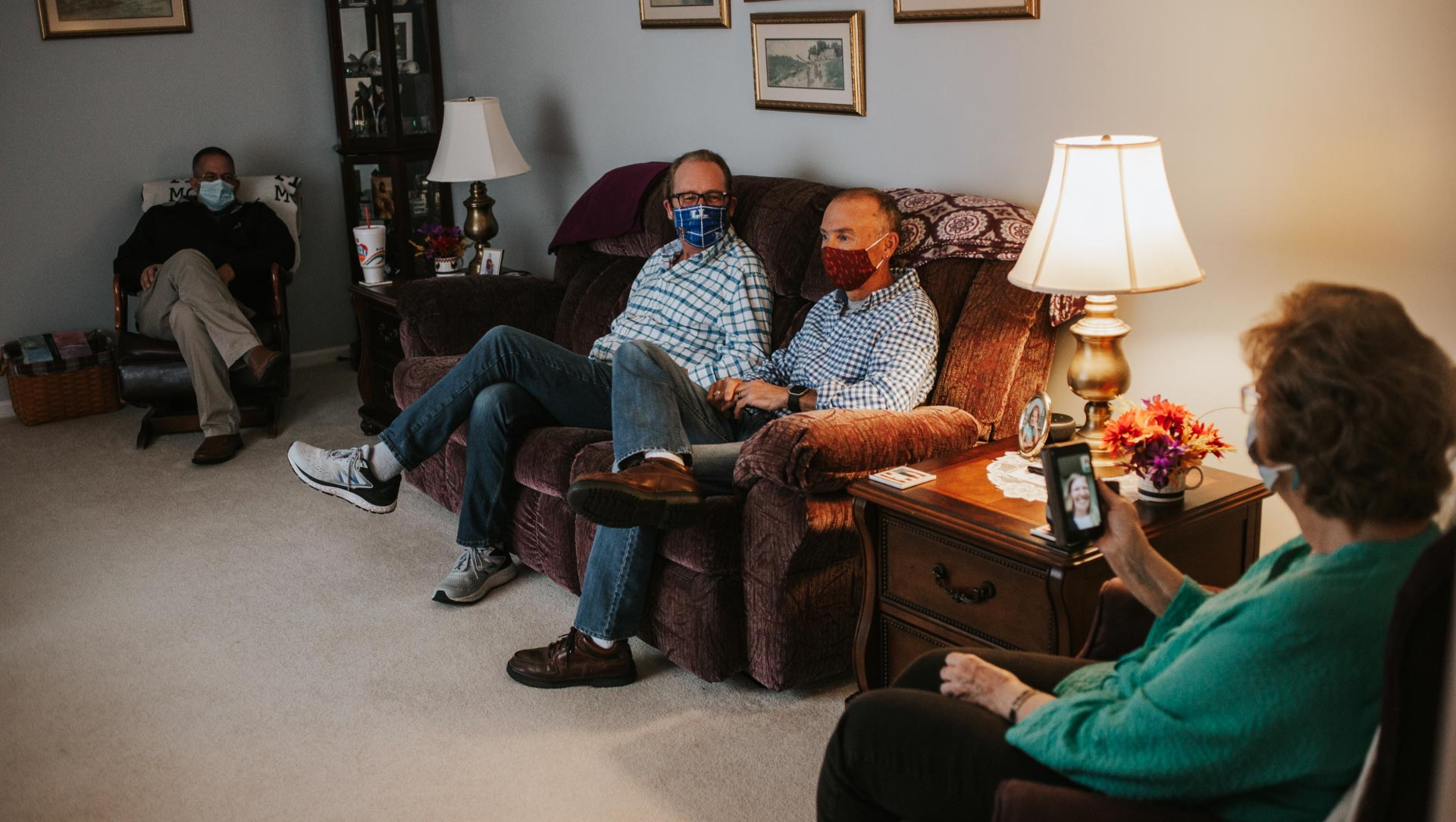 Mae sits on a single couch with her facemask, on a video call with her daughter-in-law, a young white woman with a big smile. Spread across the room are three middle-aged men sitting cross-legged with their facemasks on.
