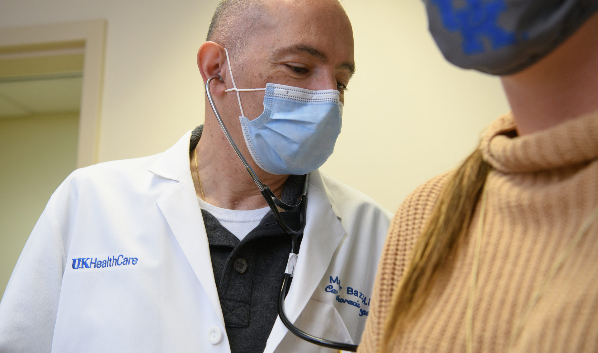 Dr. Baz, in his UK HealthCare white coat and facemask, is examining his patient with a stethoscope. The patient is a young white woman with brown hair, wearing a light brown sweater with a facemask.