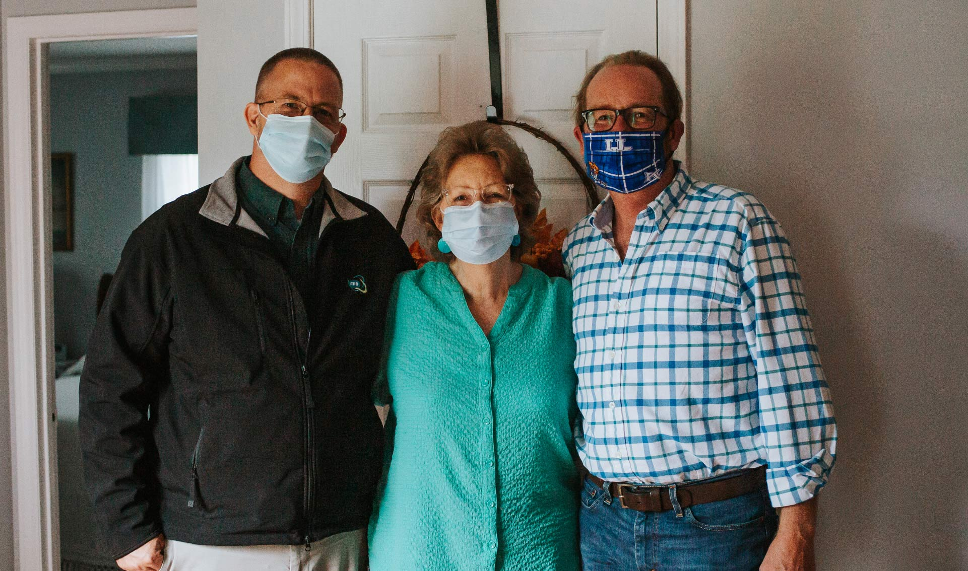 Mae standing closely between her sons. On her left is Kenneth, a middle-aged white man wearing a black jacket, glasses and a facemask. On her right is Scotty, in a white and blue checkered shirt, black framed glasses and a facemask.