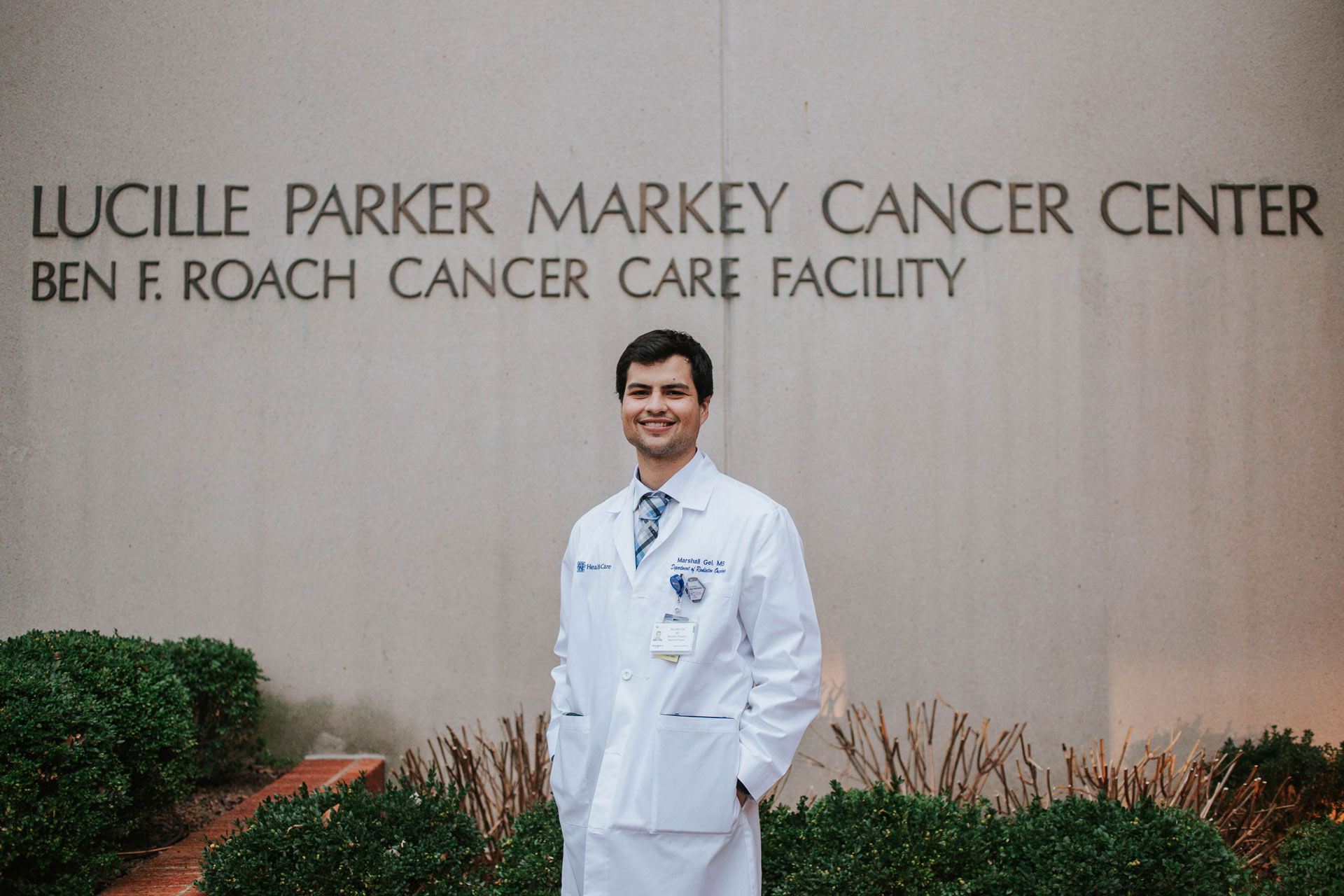 Marshall stands in front of the Lucille Parker Markey Cancer Center with his hands in his coat pocket, smiling broadly.