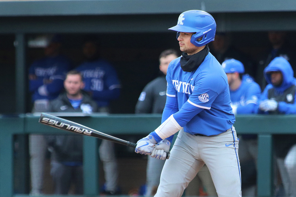 Marshall on a baseball field in his blue UK baseball uniform with a bat, ready to swing.