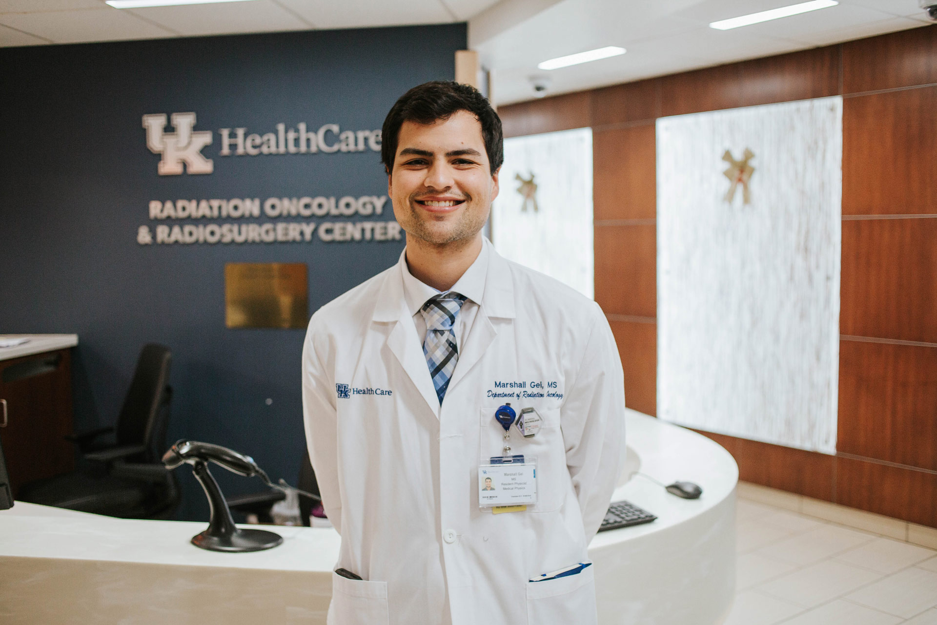 Marshall standing in the UK HealthCare Radiation Oncology and Radiosurgery Center. He is wearing a white doctor's coat and a blue plaid tie.