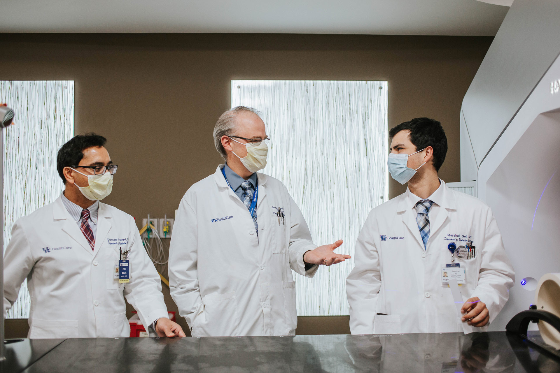 Marshall stands beside two directors of medical physics in his Radiation Oncology department: Dr. Damodar Pohkrel, middle-aged South Asian man with black hair, and Dr. Dennis Cheek, a middle-aged white man with grey hair. Both men are wearing their doctor's coats and spectacles. All three are wearing masks.