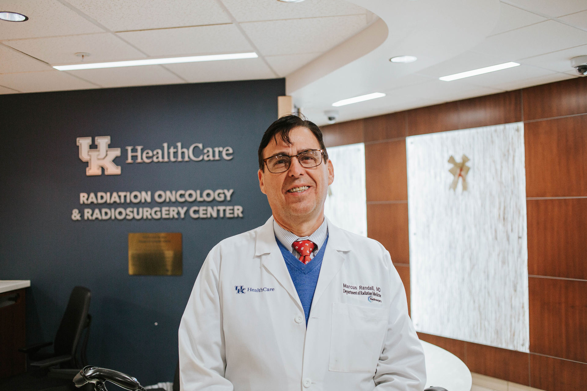 Dr. Marcus Randall, a middle-aged white man with black hair, is standing in the UK HealthCare Radiation Oncology and Radiosurgery Center. He is wearing a white doctor's coat, a blue sweater, a red tie with white polka dots and spectacles.