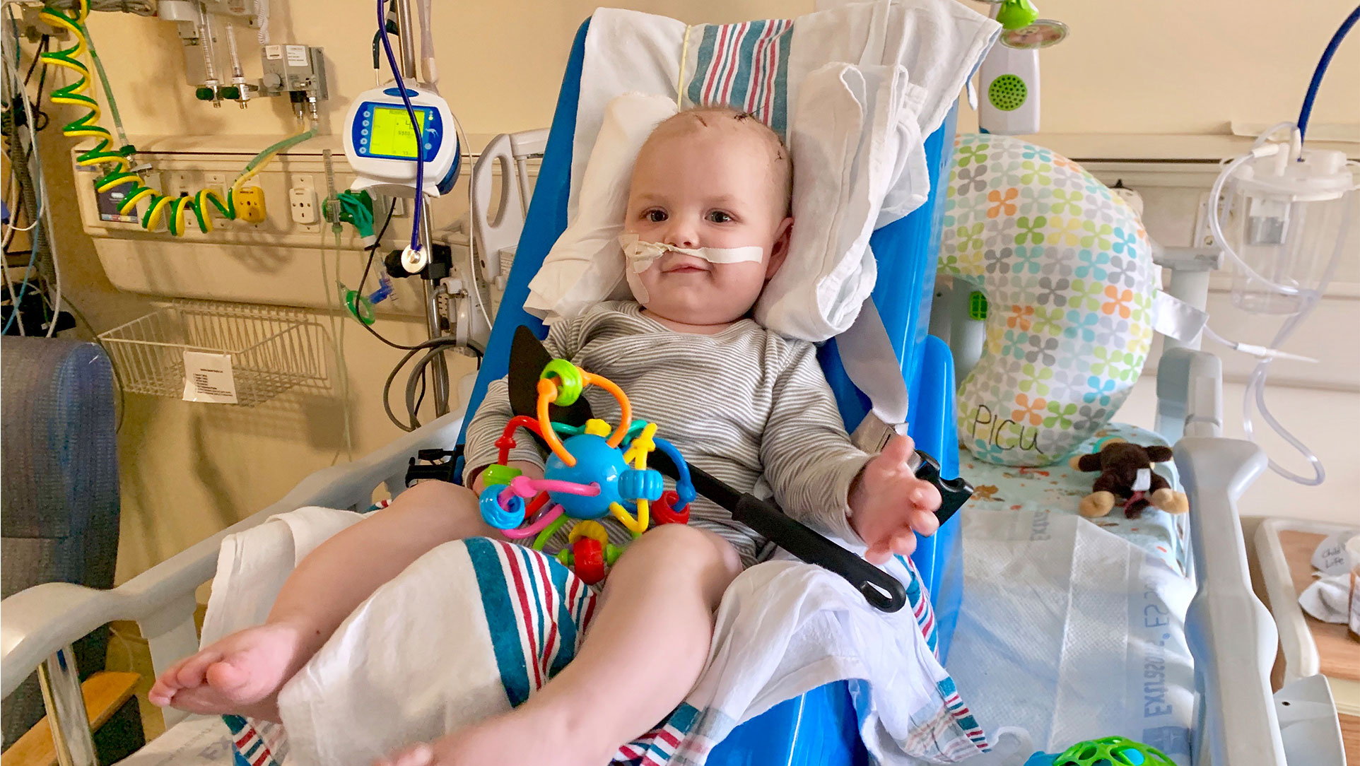 Rory is laying in his hospital bed with a colorful toy on his lap. He is wearing a grey striped outfit and has a tube in his nose.