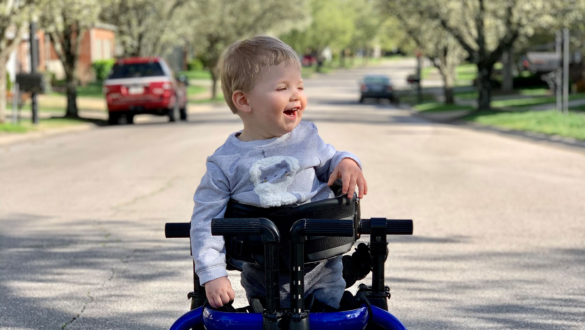 Rory stands smiling in an outside setting with the support of his gait trainer. An assistive medical device designed to train him in his walking pattern and assist with slow progressive weight bearing. He is wearing a grey lion sweatshirt with matching sweatpants.