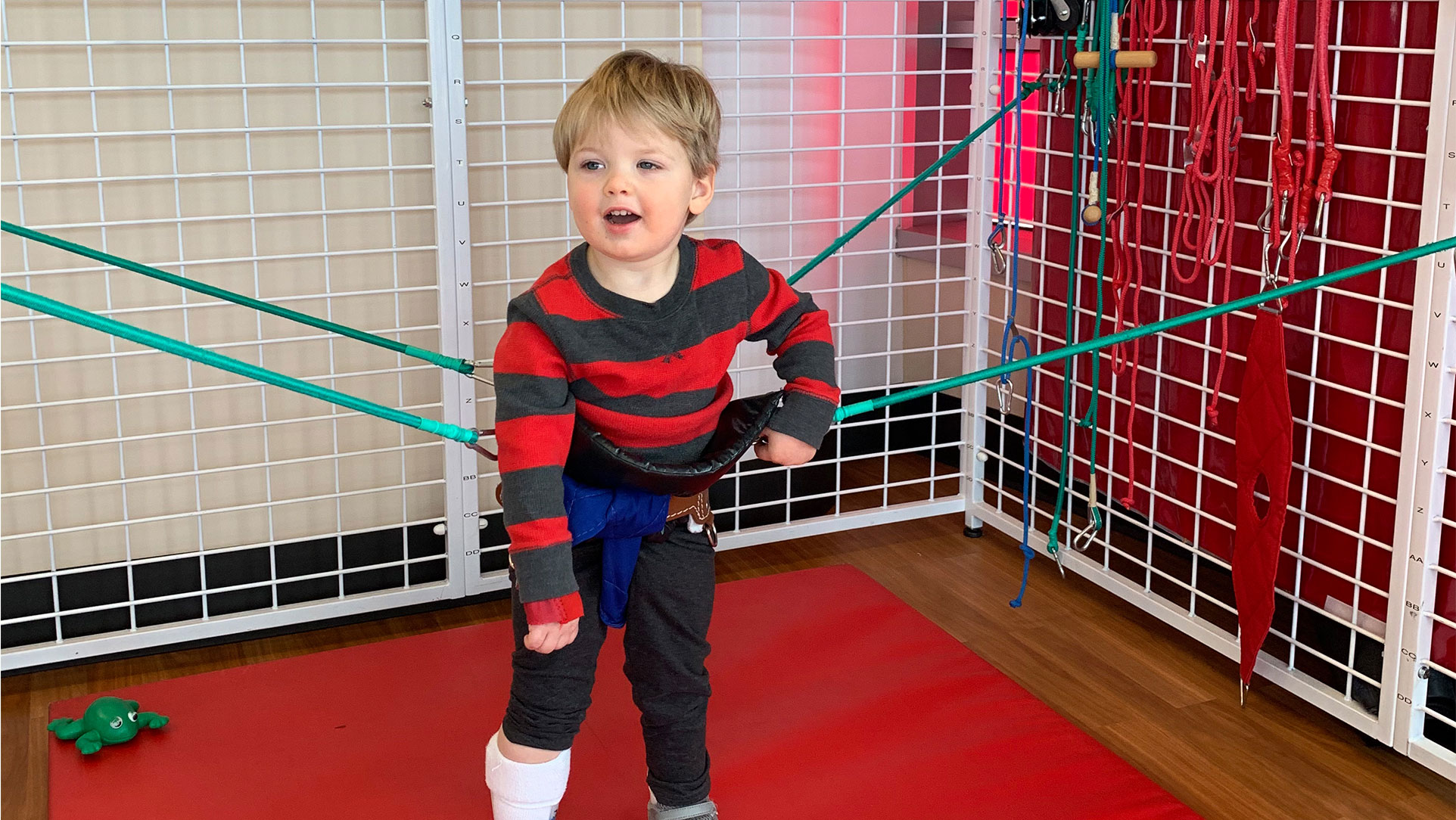 Rory at physical therapy in his gait trainer. He is wearing a dark grey and red striped shirt with dark grey pants.