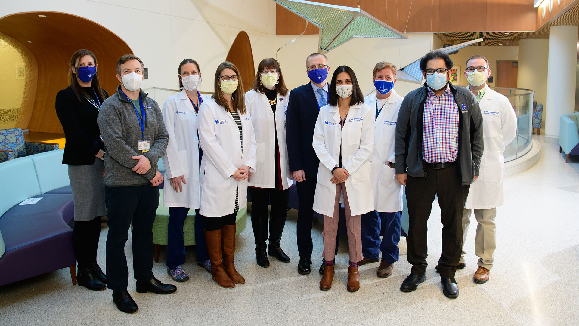 Rory's team of medical workers—men and women—are standing side by side inside the lobby of Kentucky Children's Hospital. They are all wearing facemasks and some are in doctor's coats.