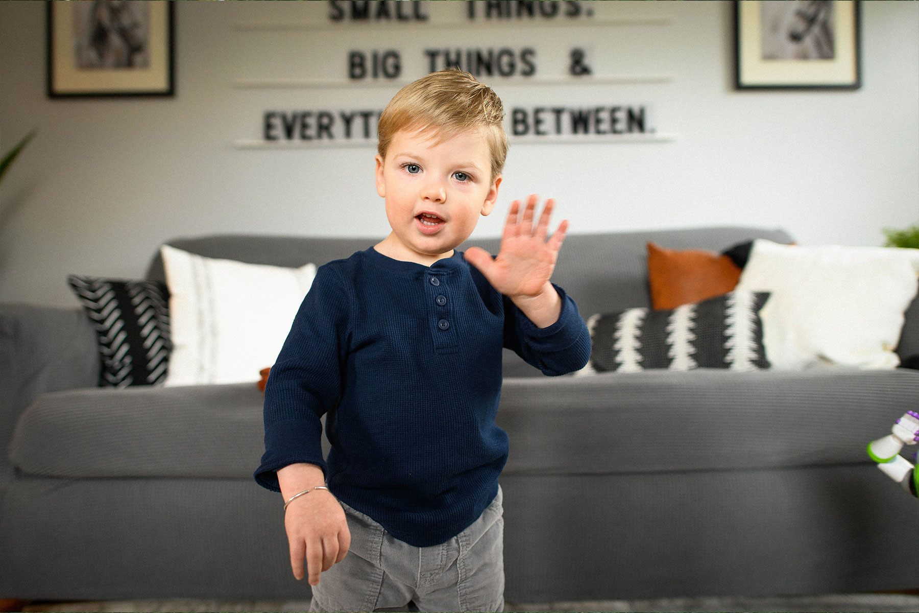 Rory McCamish, a white toddler with blonde hair, blue eyes, and a round face, is standing in his living room waving. He is wearing a navy blue shirt and grey pants.