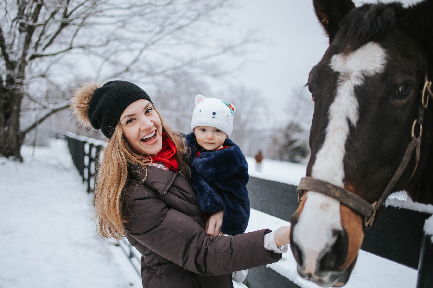 Dr. Tessa London, a middle-aged white woman with long brown wavy hair, stands in an snowy outdoor setting. She is smiling widely as she holds her youngest daughter and stands next to a horse. Both Dr. London and her daughter are wearing beanies and winter jackets.