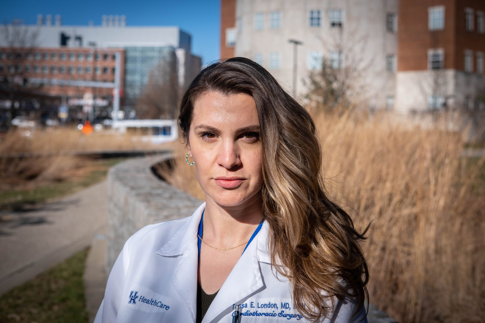 A portrait of Dr. London, standing outside the hospital in a white coat and a blue shirt. Her hair is loose and pushed to one side, and she is wearing a small gold chain and green hoop earrings.