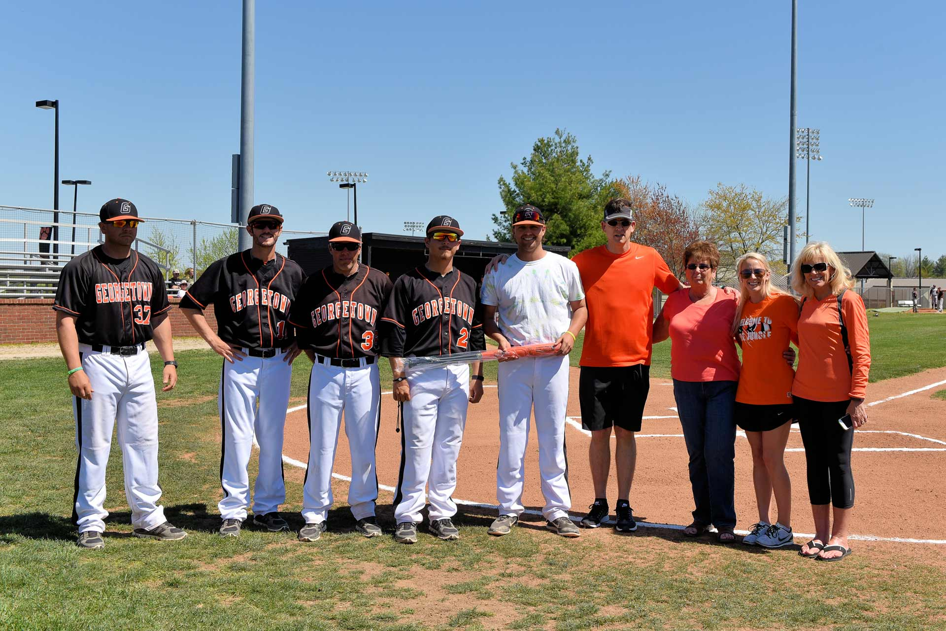 Trent poses for a photo on a baseball field, surrounded by his teammates and his family members, holding a baseball bat.