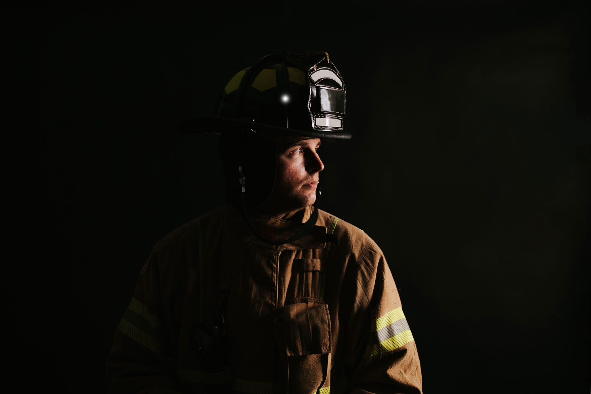 Trent in his firefighting gear and uniform, in front of a black background. His head is turned to the side for a profile view.
