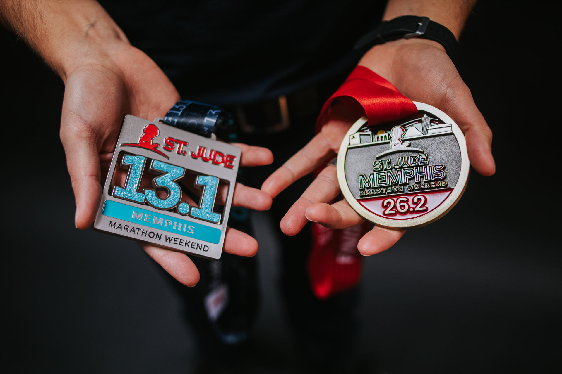 Trent holds out two medals in his hands. On his left hand is a silver medal from a St. Jude 13.1-mile half marathon, and on his right hand is a gold medal from a St. Jude 26.2-mile marathon.