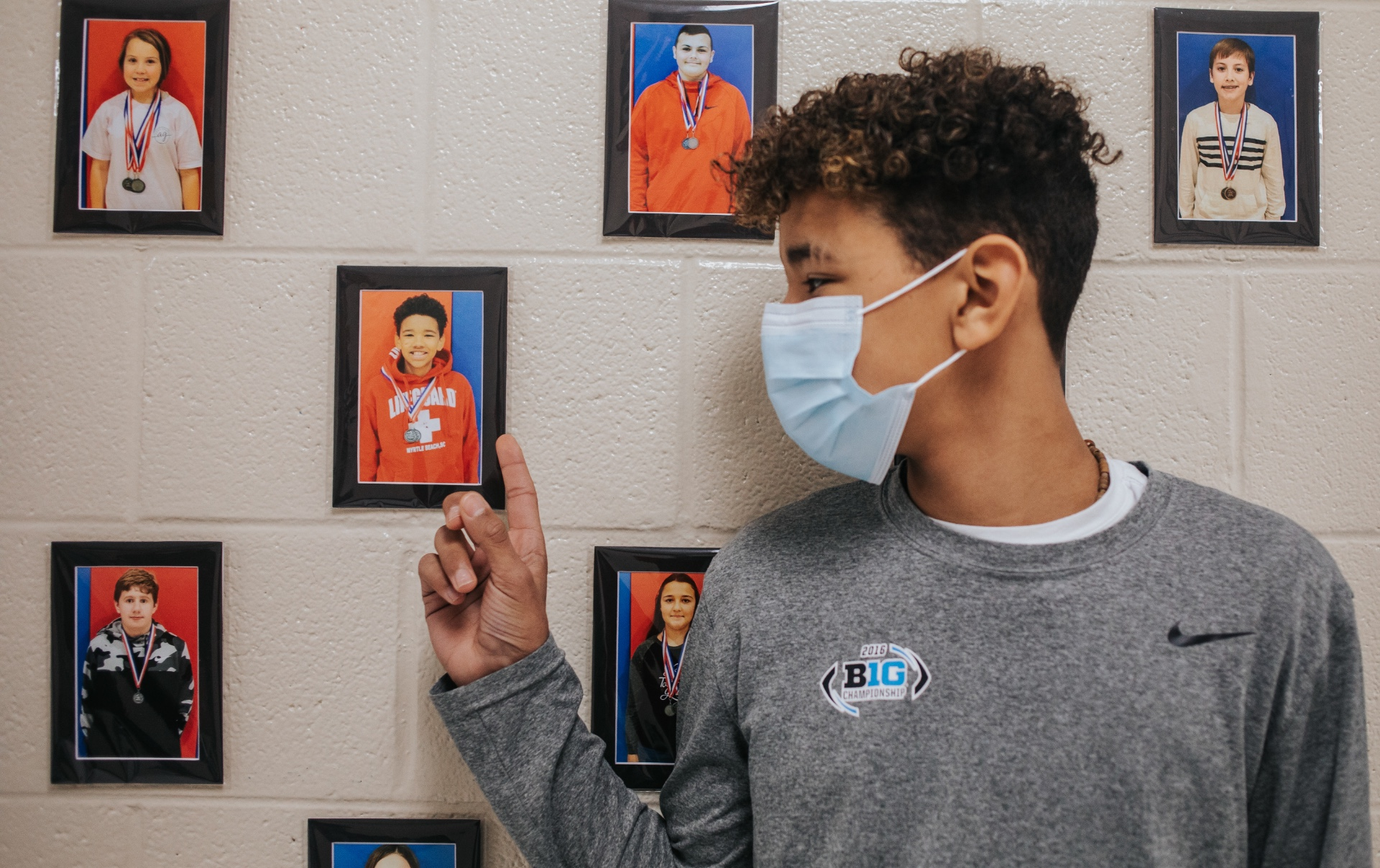AJ wears a mask and points at a photo of himself when he was younger.