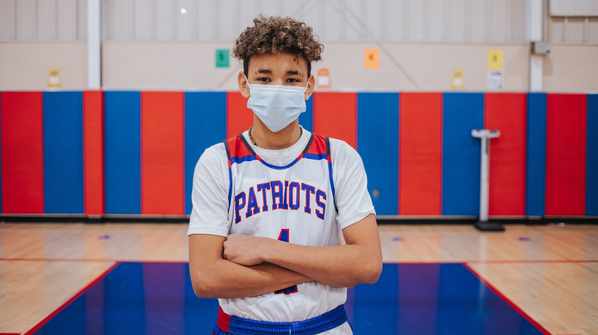 AJ stands in the middle of the basketball court in his white Patriots team uniform and a face mask. He has his arms crossed in front of his chest.