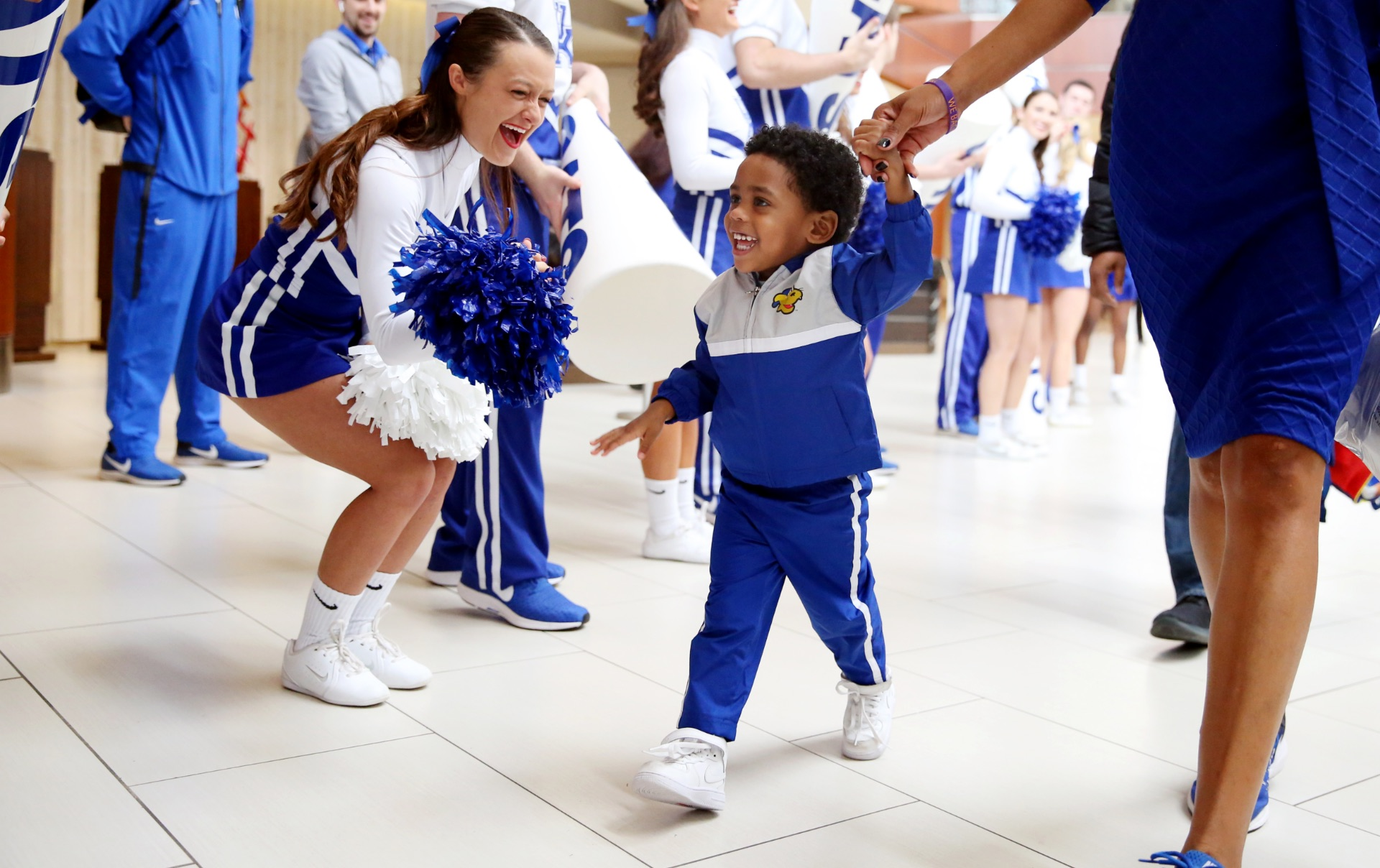Jackson walks alongside his mother, Coach Kyra Elzy, with UK cheerleaders on one side cheering him on. He is smiling widely and wearing a blue and white tracksuit.