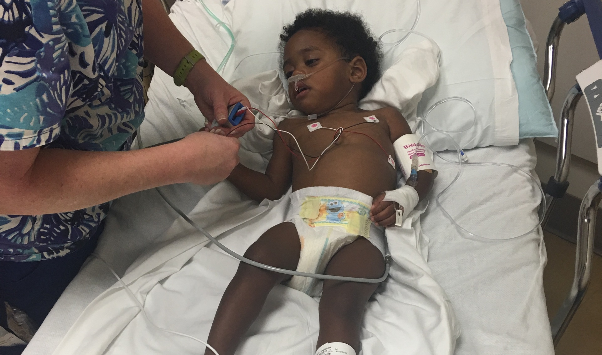 A photo of Jackson when he was in the hospital as a two-year-old, with a nurse at his side adjusting the wires attached to body to monitor his vitals.
