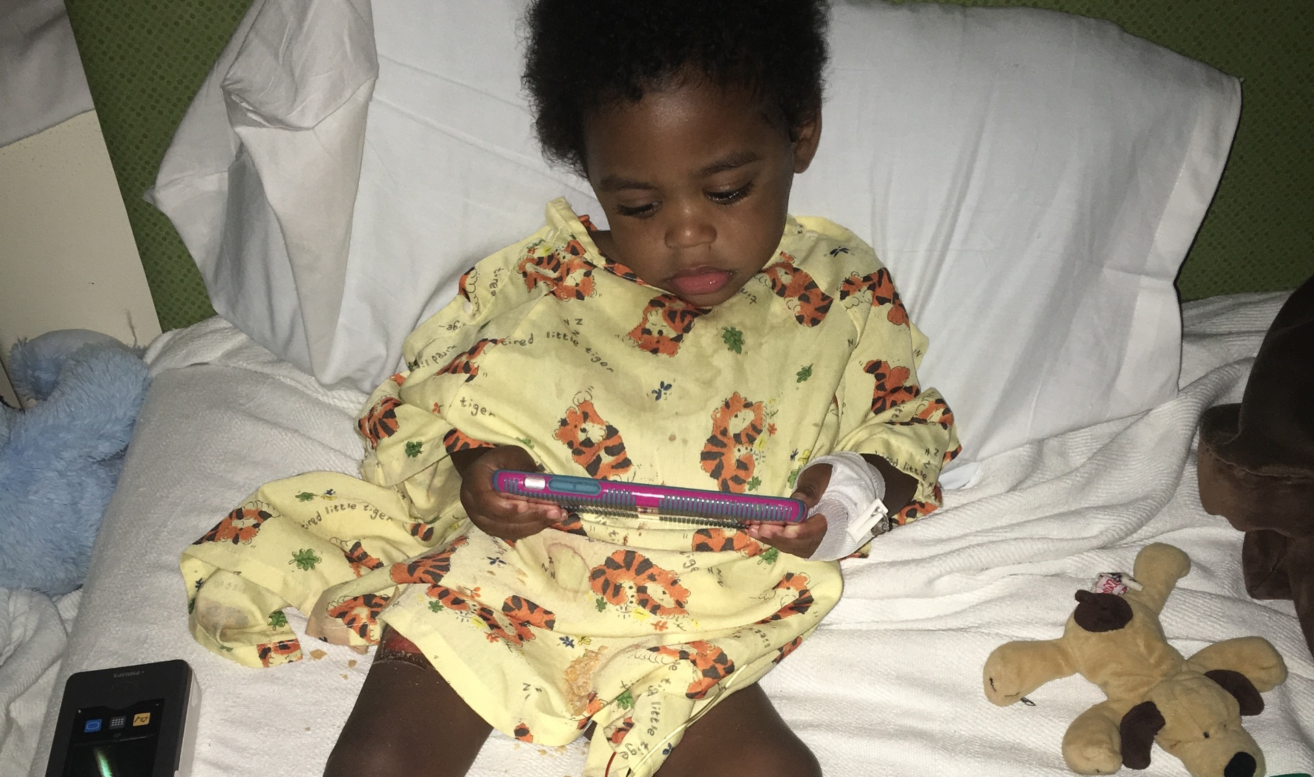 Jackson sits on his hospital bed, surrounded by his toys as he watches something on a phone. He is wearing a hospital gown with tigers on it.