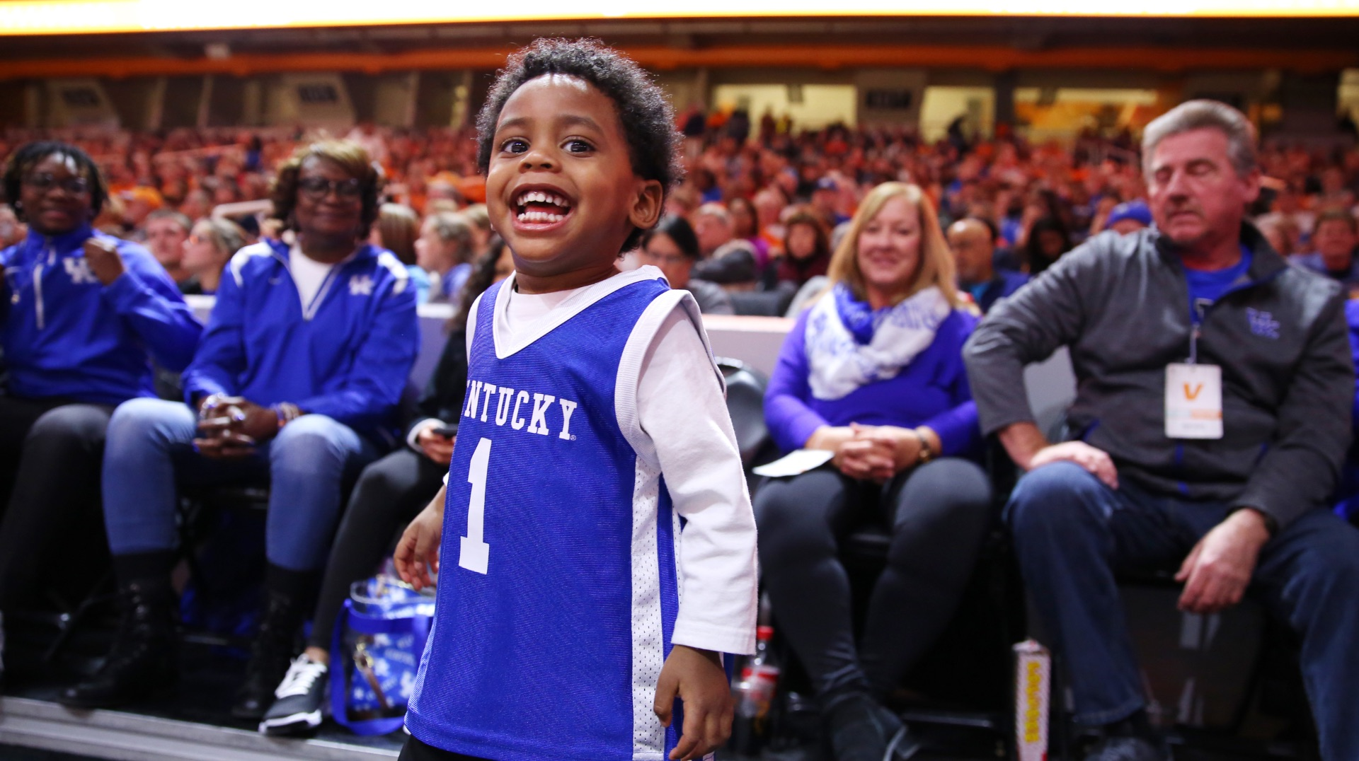 Jackson stands on the sidelines at a basketball game, smiling widely. There are several seated people behind him wearing blue and white UK colors. Jackson is wearing a Kentucky basketball jersey over a long-sleeve white shirt.