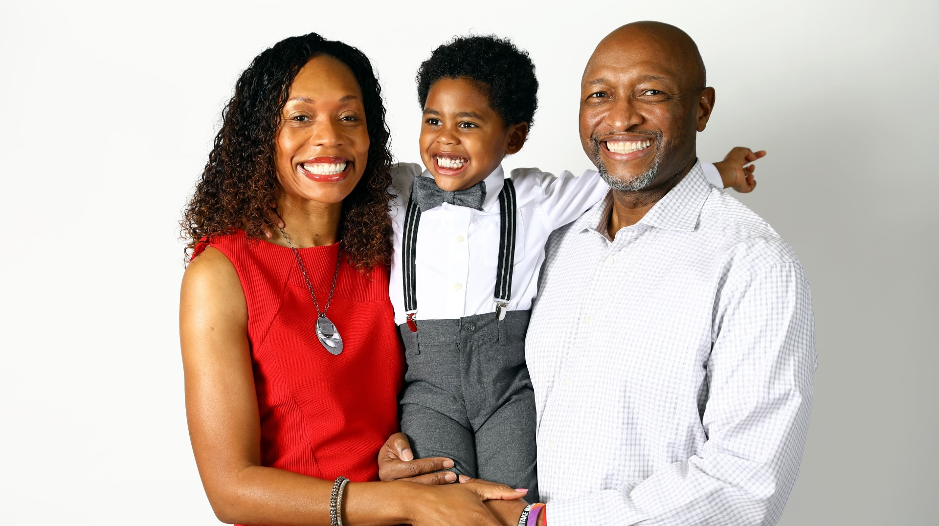 Jackson smiles widely as he is carried in between his mother, Coach Kyra Elzy—an African American woman with brown hair in a red dress—and his father, Dexter Lander, an African American man in a white button-down shirt