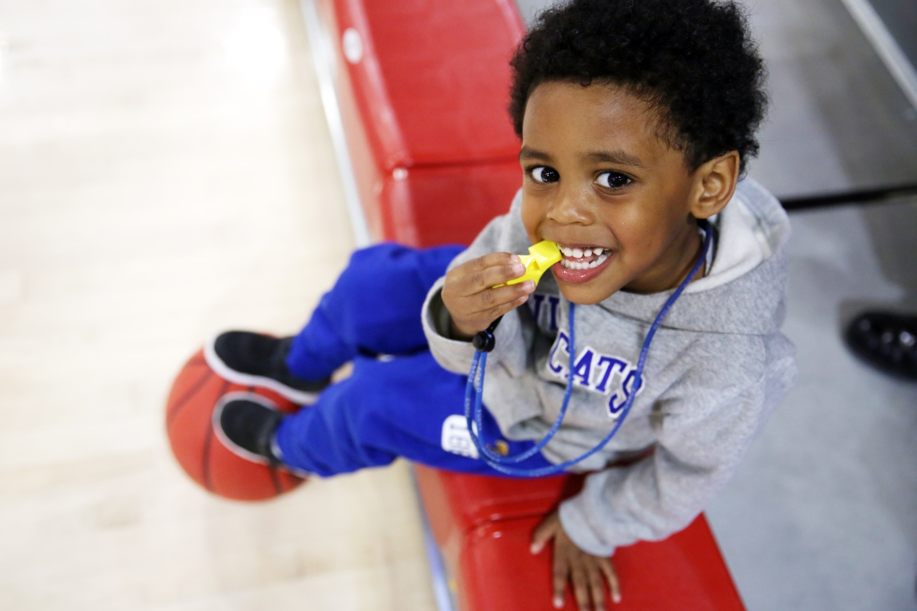 Jackson Lander, a five-year-old African American boy with curly black hair. He is sitting with a basketball at his feet, and a yellow whistle on his mouth as he smiles widely. He is wearing blue pants and a grey hoodie with the University of Kentucky 'Cats' emblem on it.