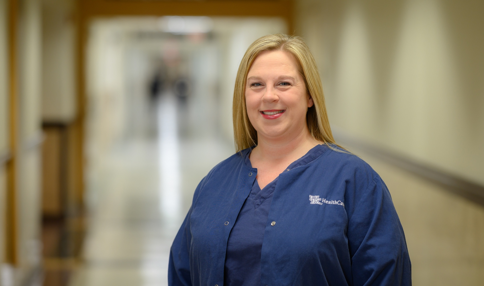 Allison Pinkston, a middle aged blonde white woman, stands smiling in the hospital hallway. She is wearing blue scrubs, as part of the required uniform.