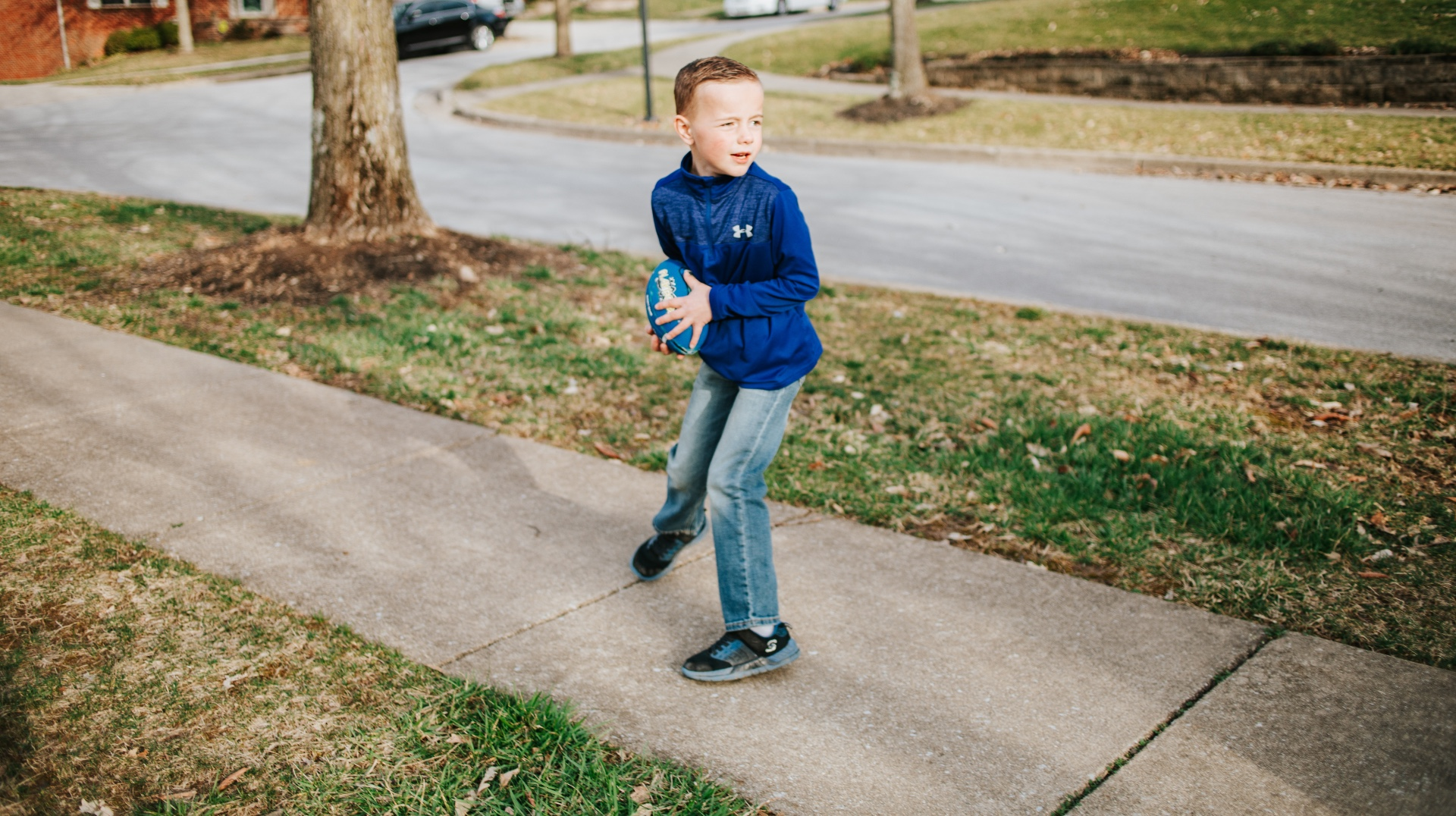 Henry stands on the pavement outside. He is about to throw a blue football and poses in the position to do so.