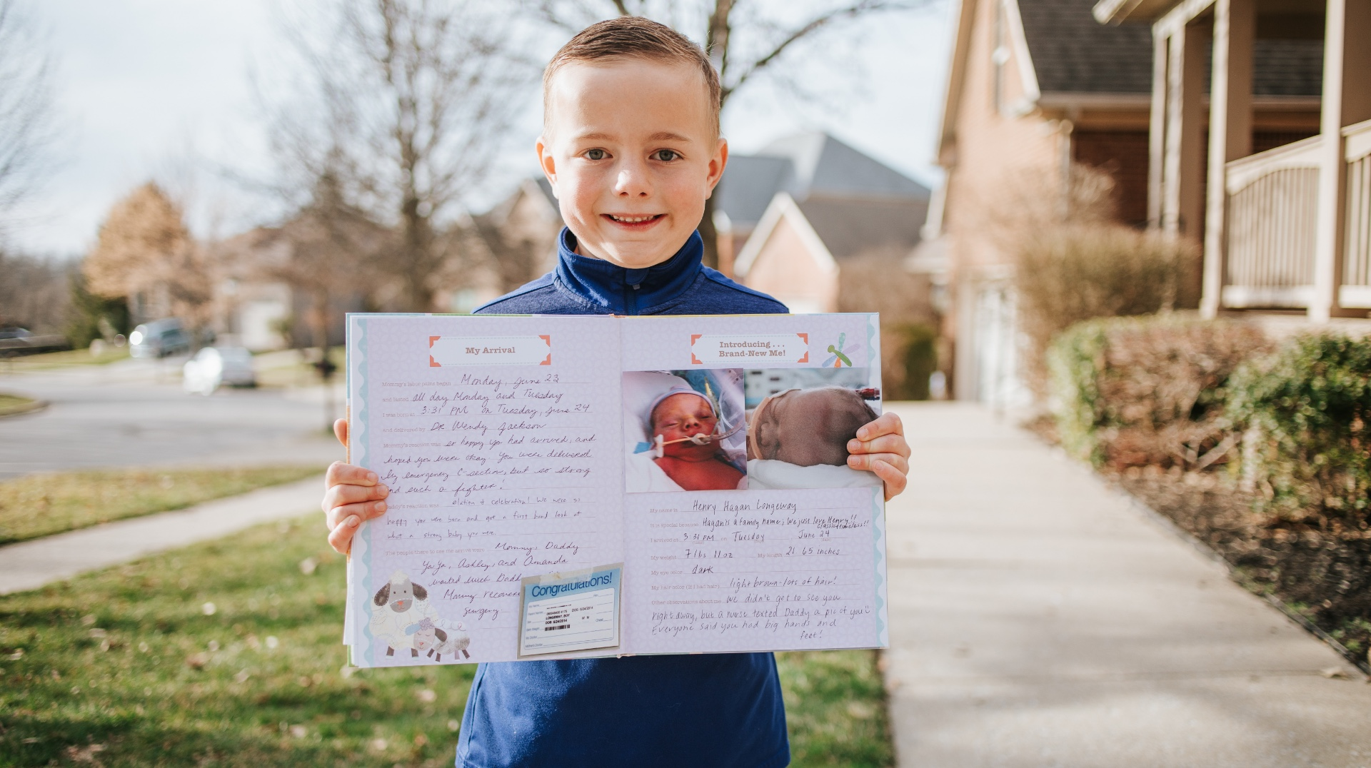 Henry stands outside with a big smile as he holds up a diary with writings and images from his experience as a baby.