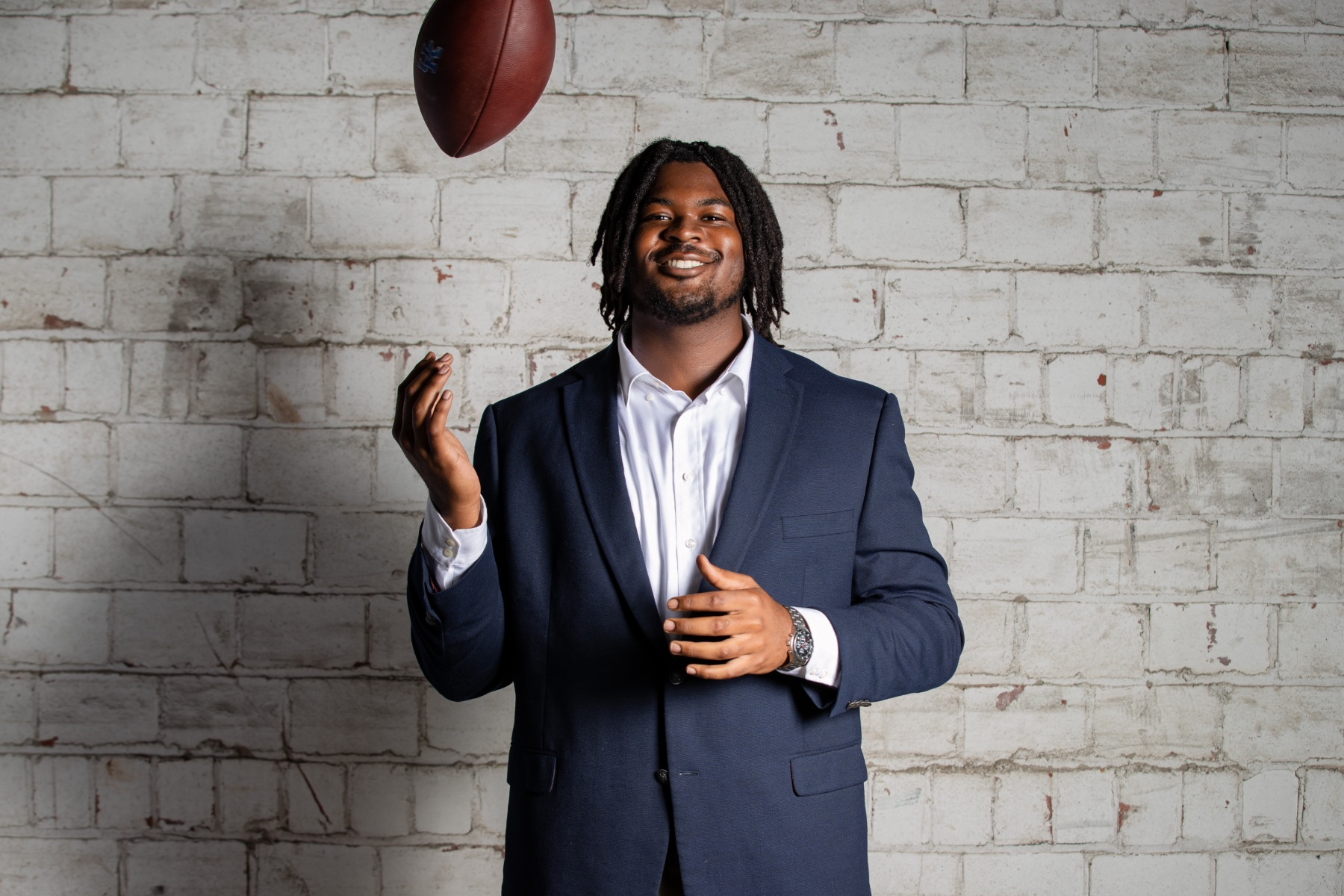 Kenneth Horsey, a young black man with dreadlocks, stands and smiles as he flips a football in the air. He is wearing a grey blazer, white button-down, and silver watch.