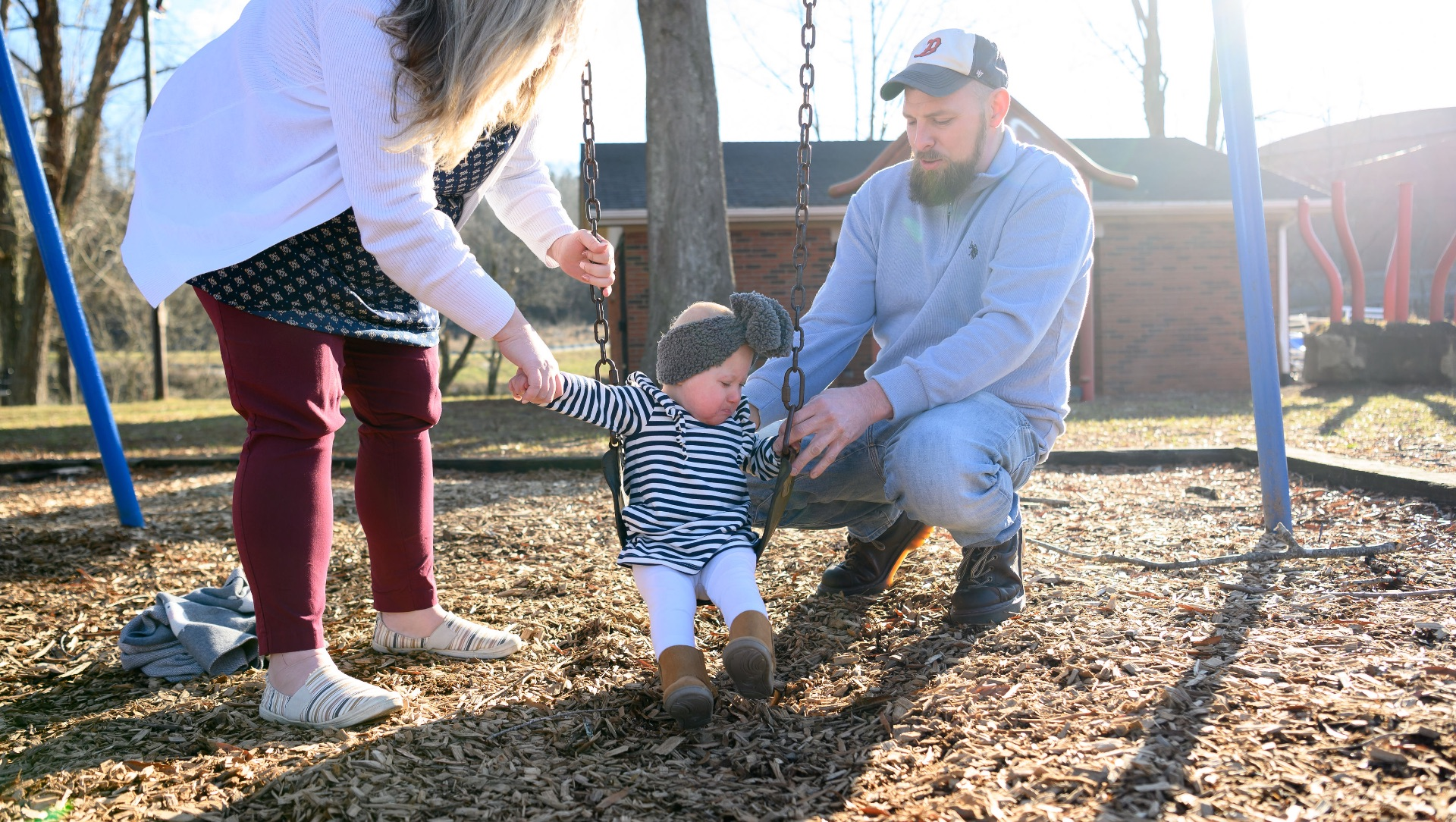 MaKenzie sits outside on a swing, flanked by her mother, Felicia, and her father, Timothy, a middle aged white man. He is wearing a light blue sweater, a grey and white baseball cap with blue jeans.